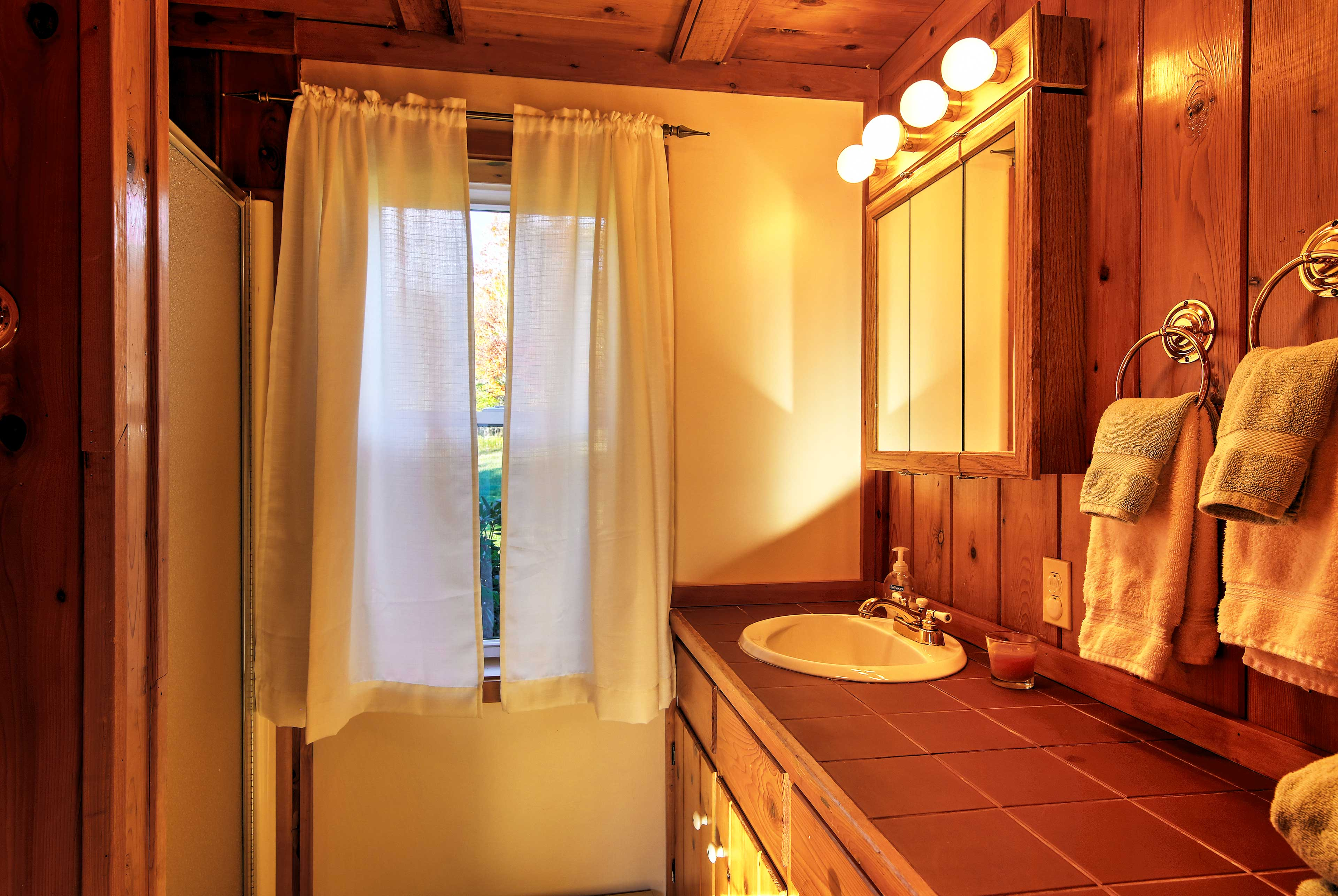The first bathroom is equipped with a walk-in shower and single vanity.