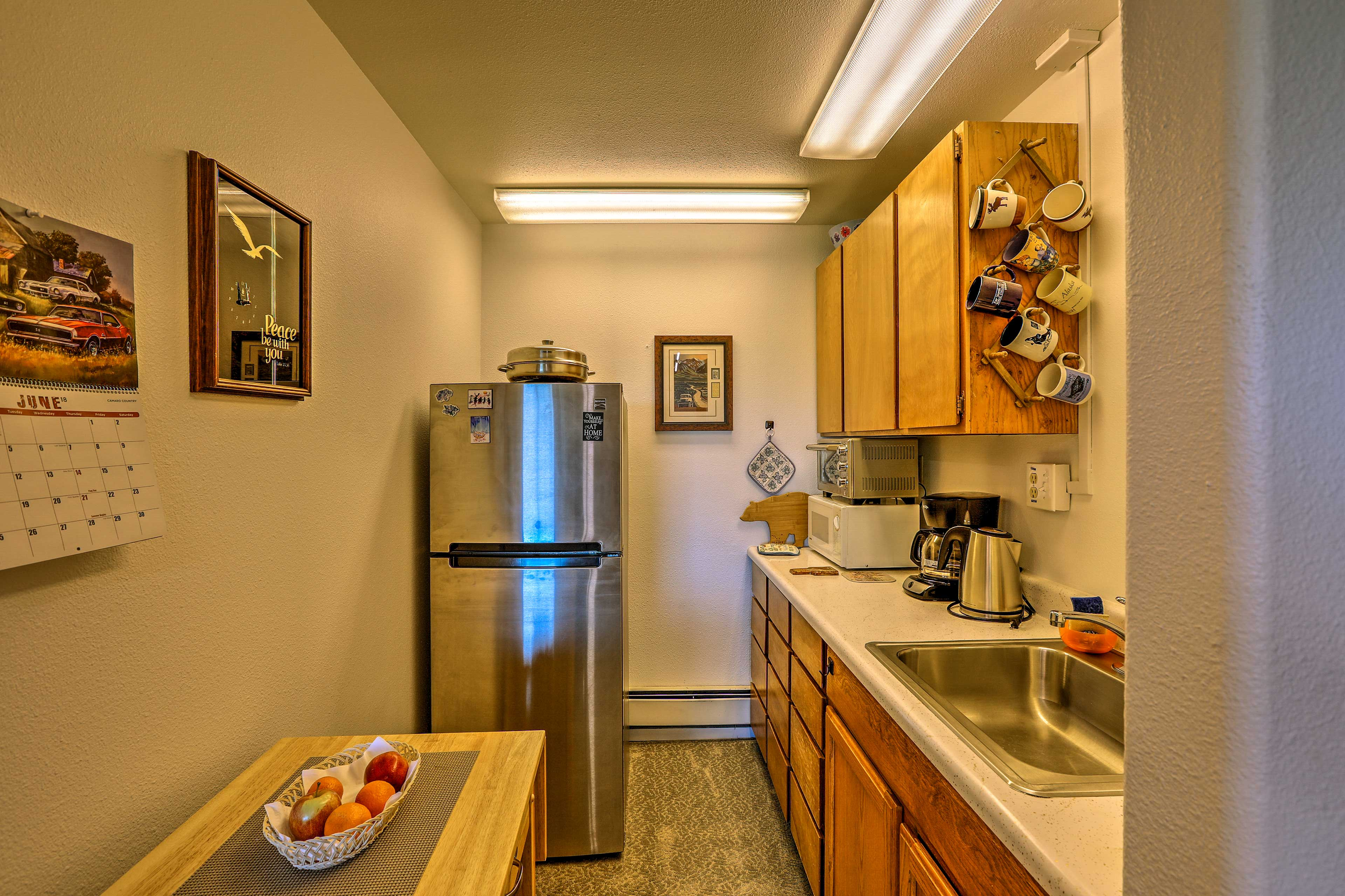 The well-equipped kitchen has a fridge, toaster oven, and coffee maker.