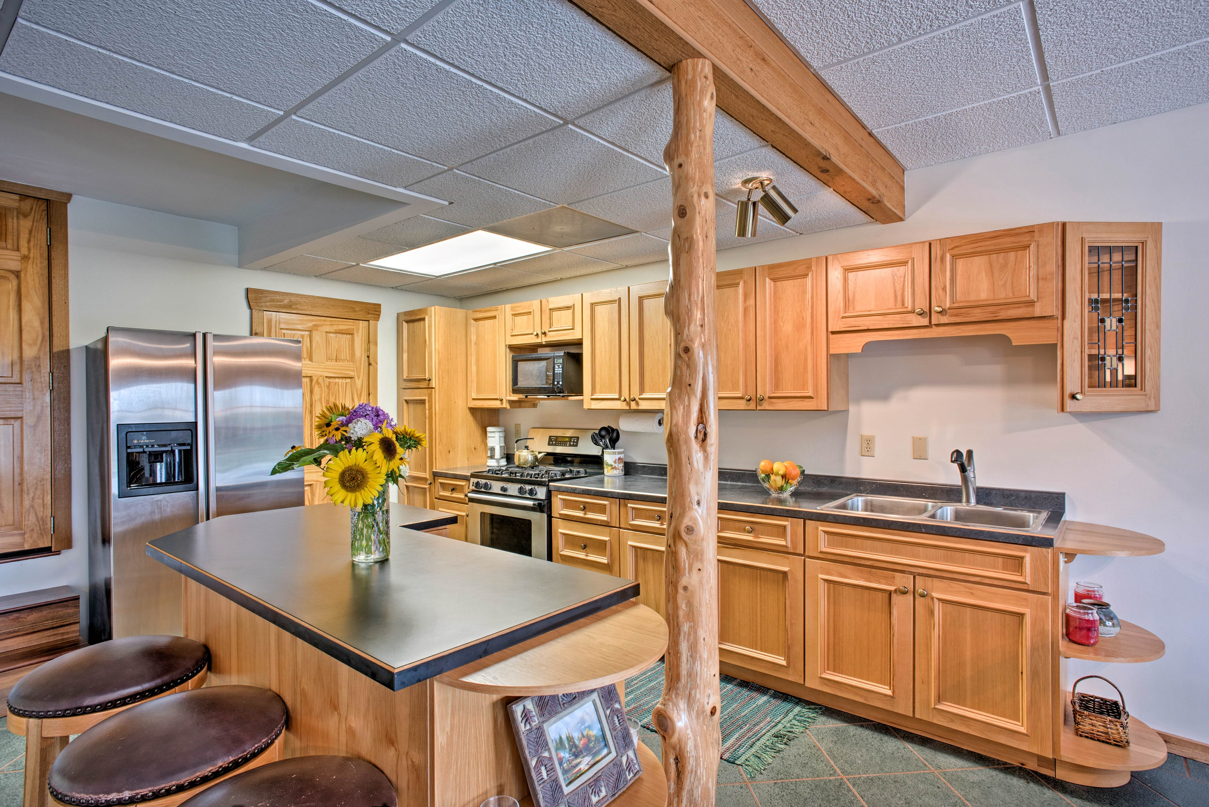 The kitchen is fully equipped with stainless steel appliances and cookware.