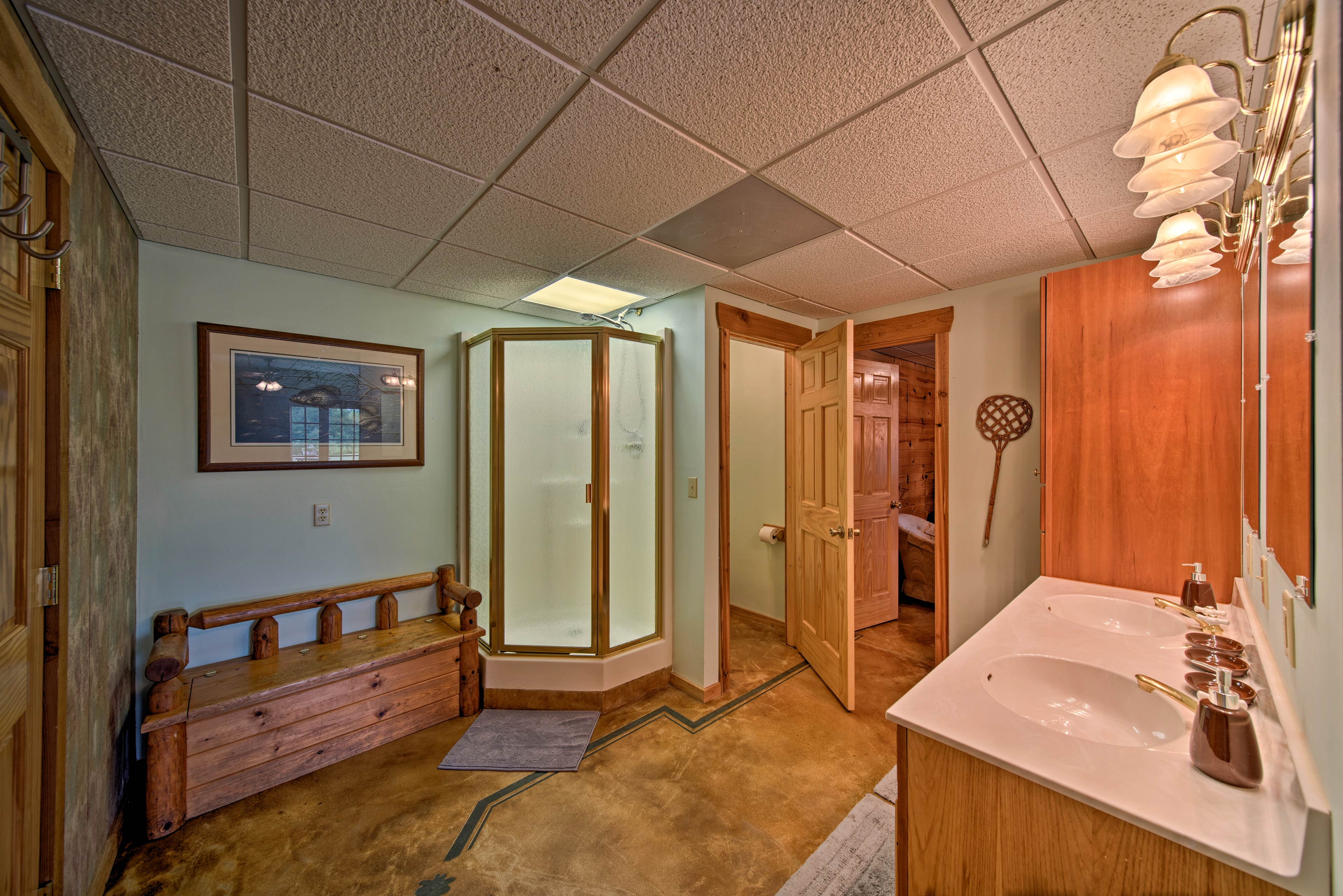 The bathroom hosts a double sink and walk-in shower.