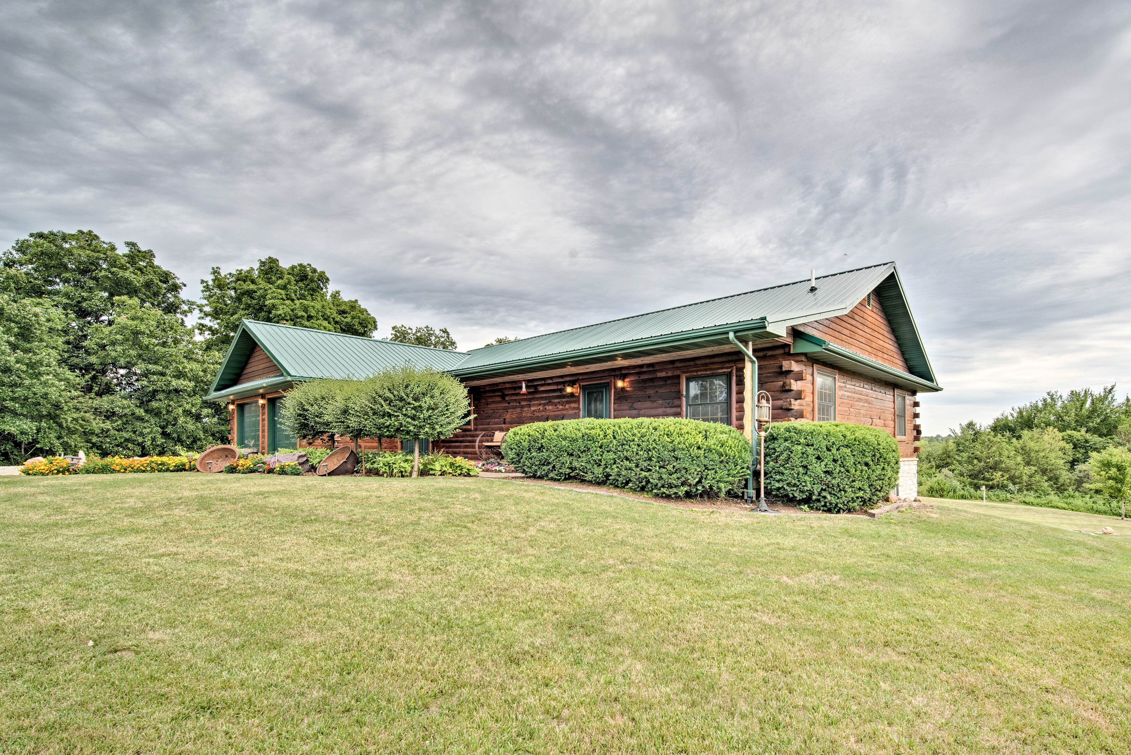 The home is surrounded by lush grass and soothing lake views.