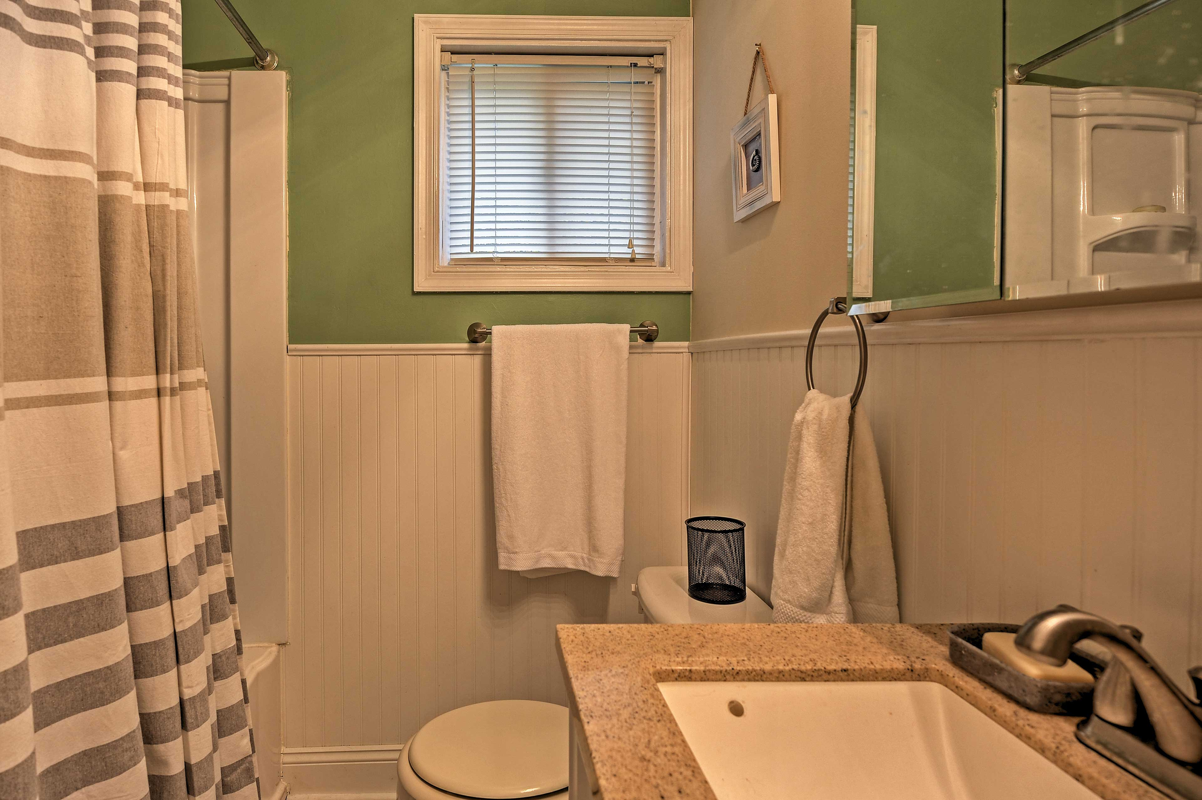 The home's bathroom features a shower/tub combo and granite sink.