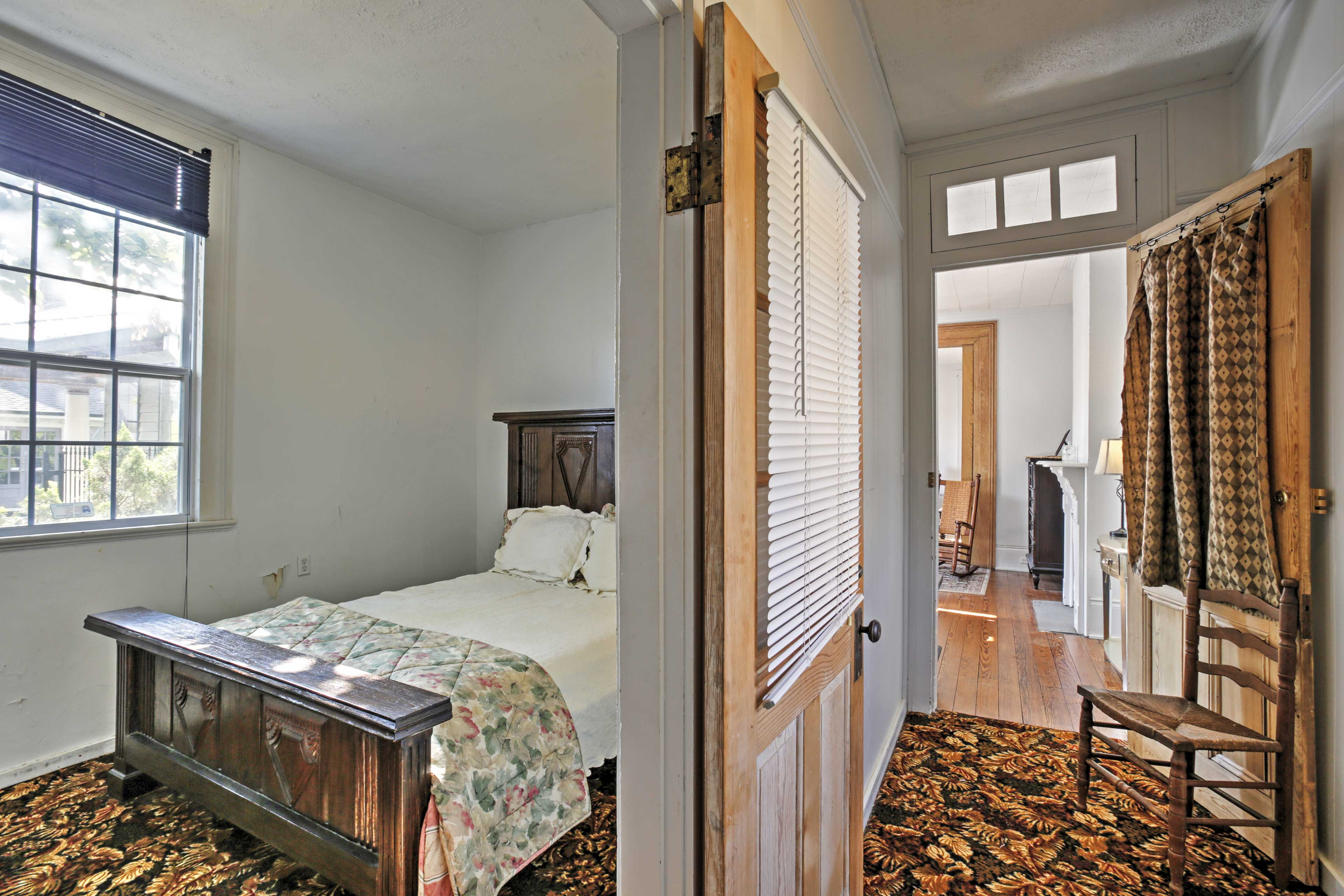 The second bedroom features a queen bed set on an antique bed frame.