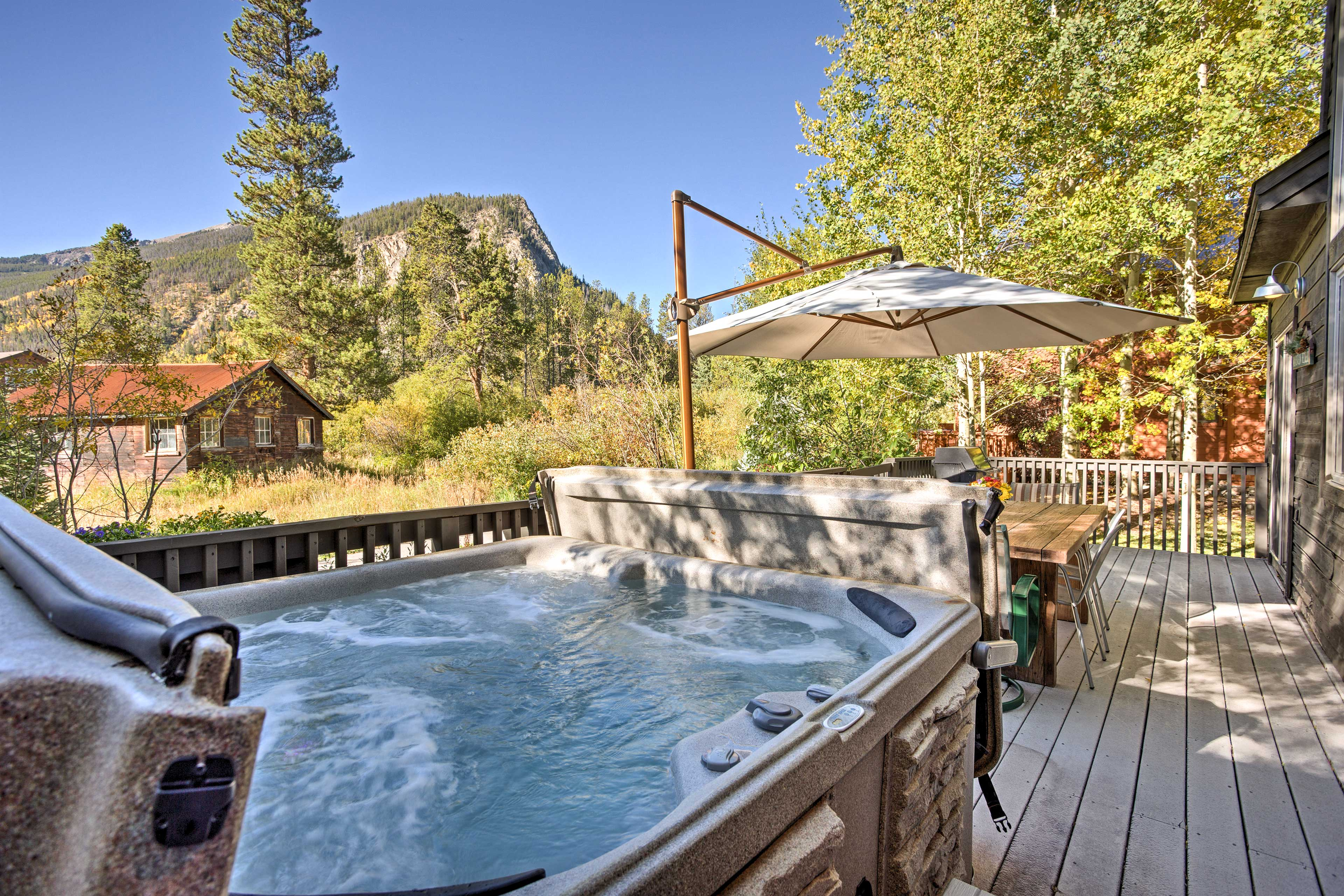 The home features a spacious back deck with a private hot tub, sauna and mountain views.
