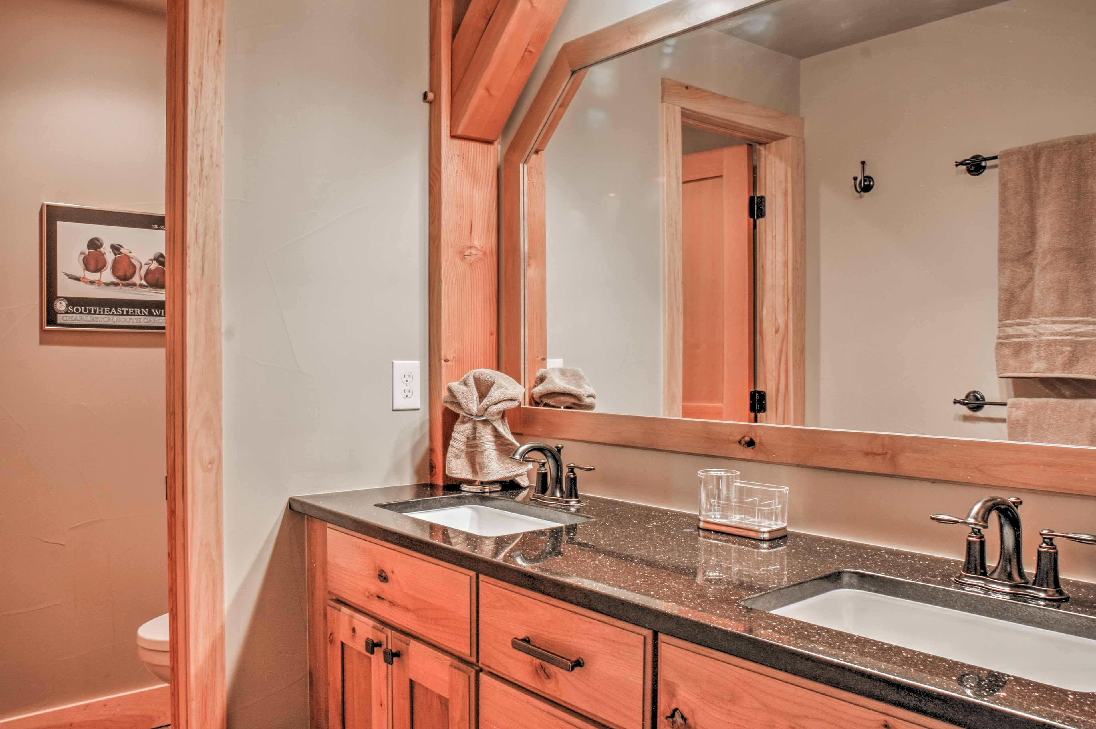 The first bathroom is equipped with a his-and-hers vanity sink and shower.