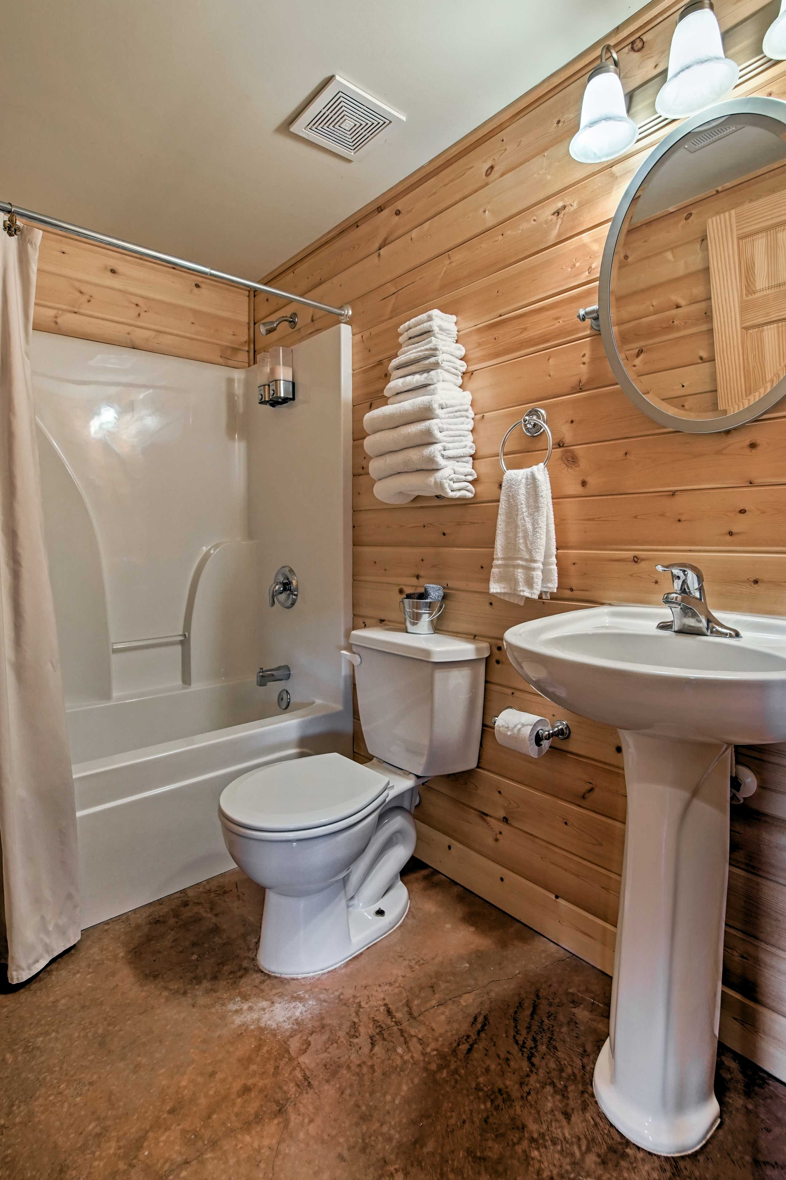 A shower/tub combo and plenty of towels are in the bathroom.