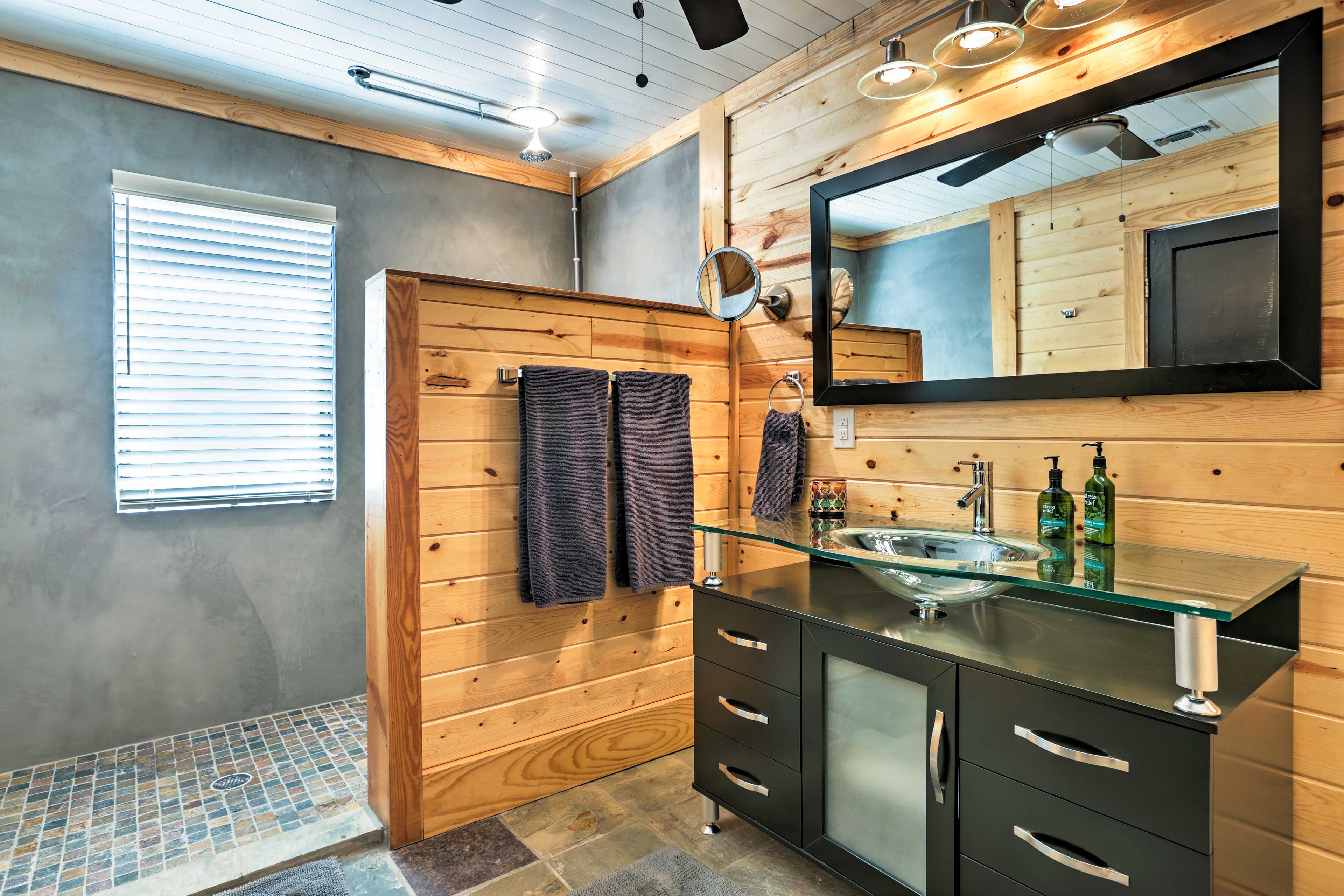The first bathroom offers a walk-in shower and exposed wood accents.