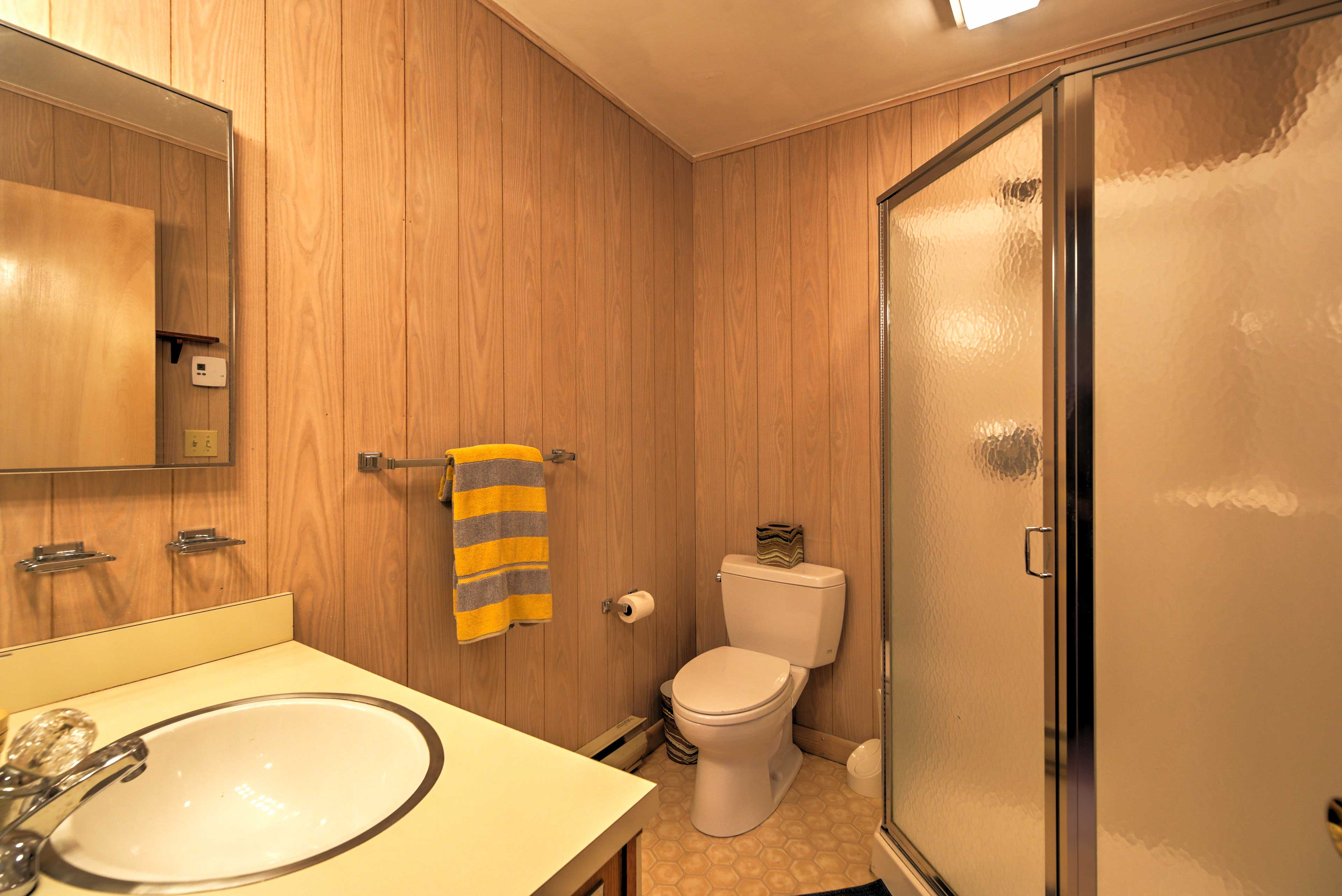 This en-suite bathroom features a spacious walk-in shower and warm wood paneling