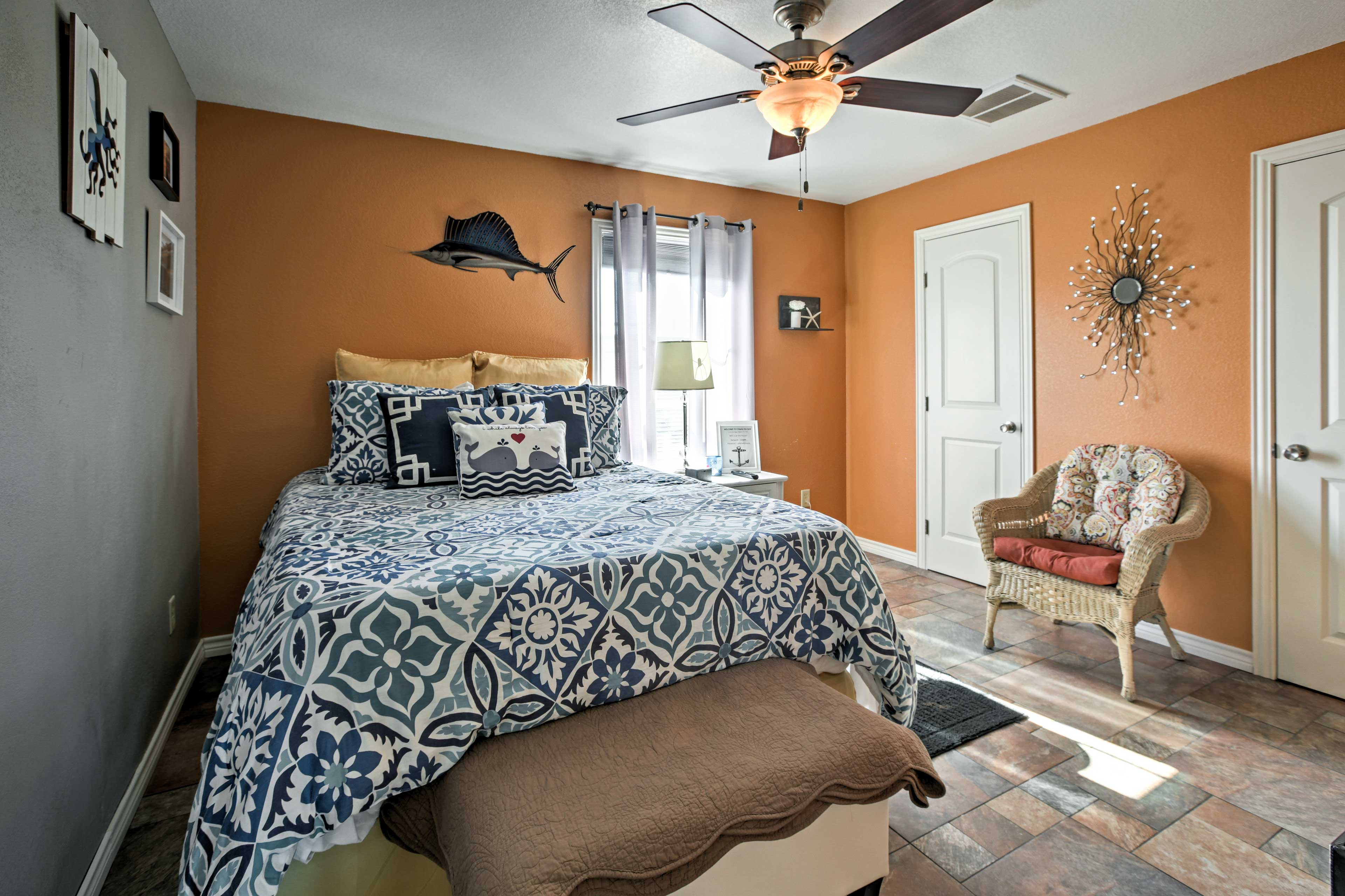 The second bedroom features a bright pop of color and a comfortable queen bed.