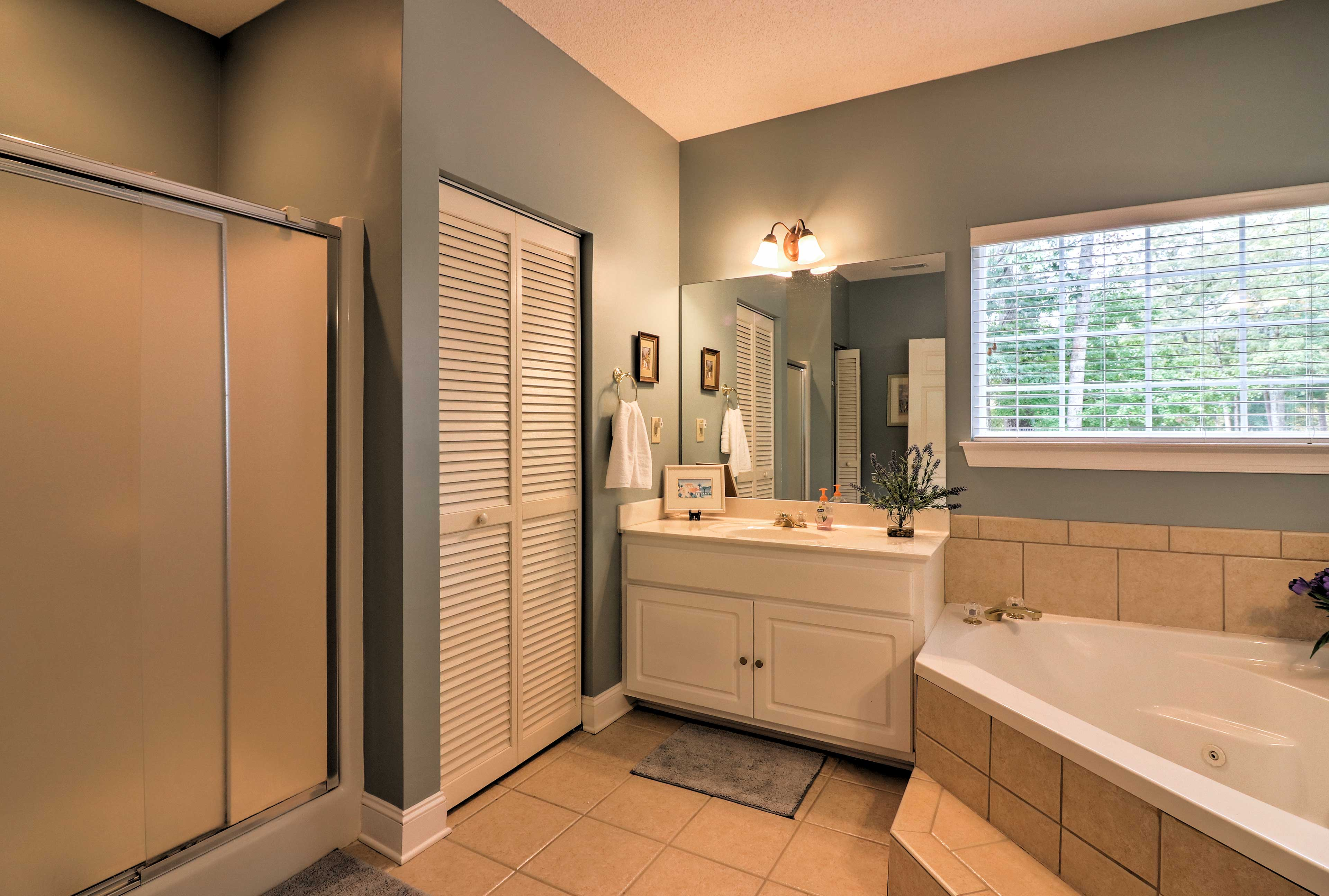 The en-suite master bathroom offers a walk-in shower and a separate tub.