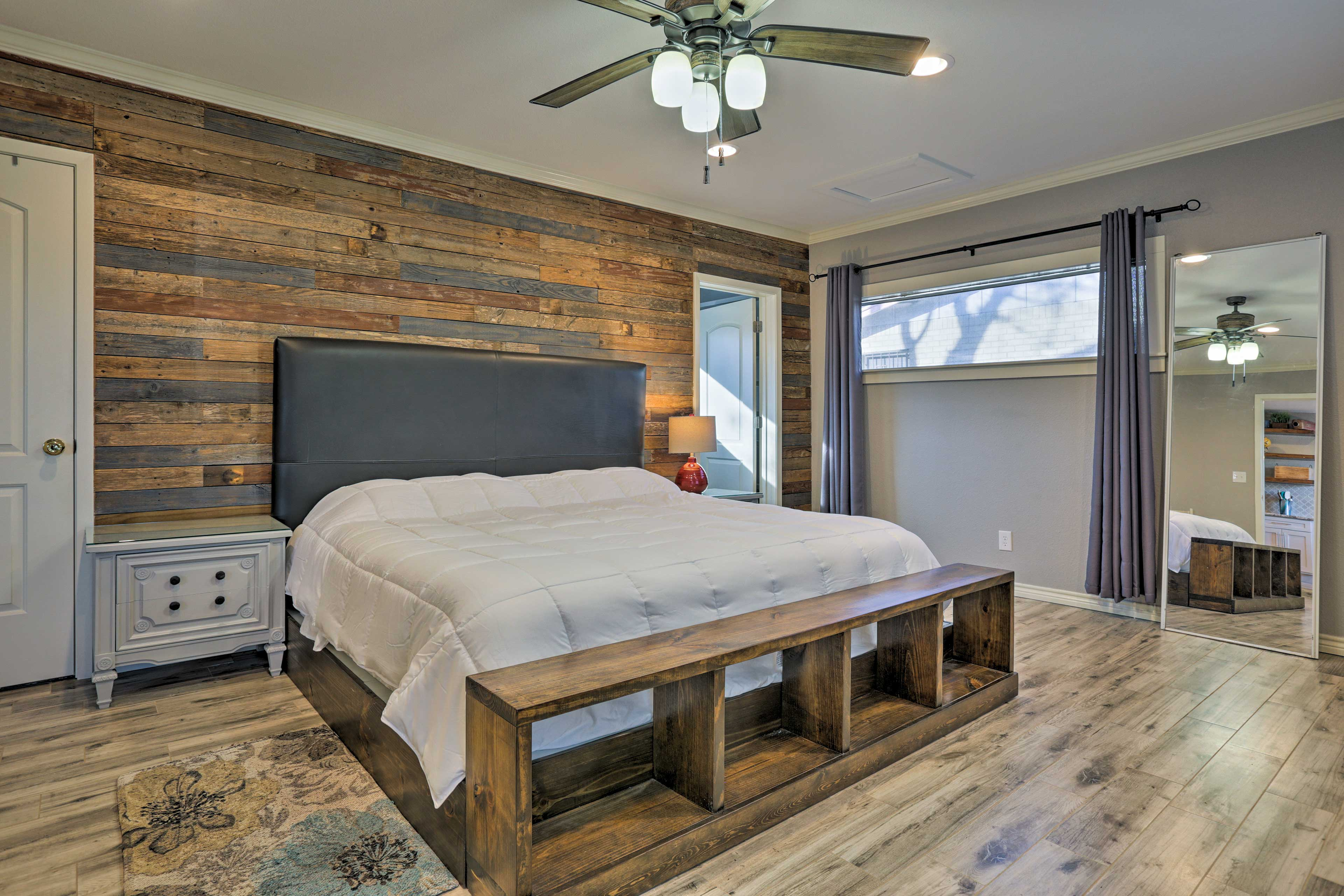 The master bedroom is backdropped by a refurbished barnwood wall.