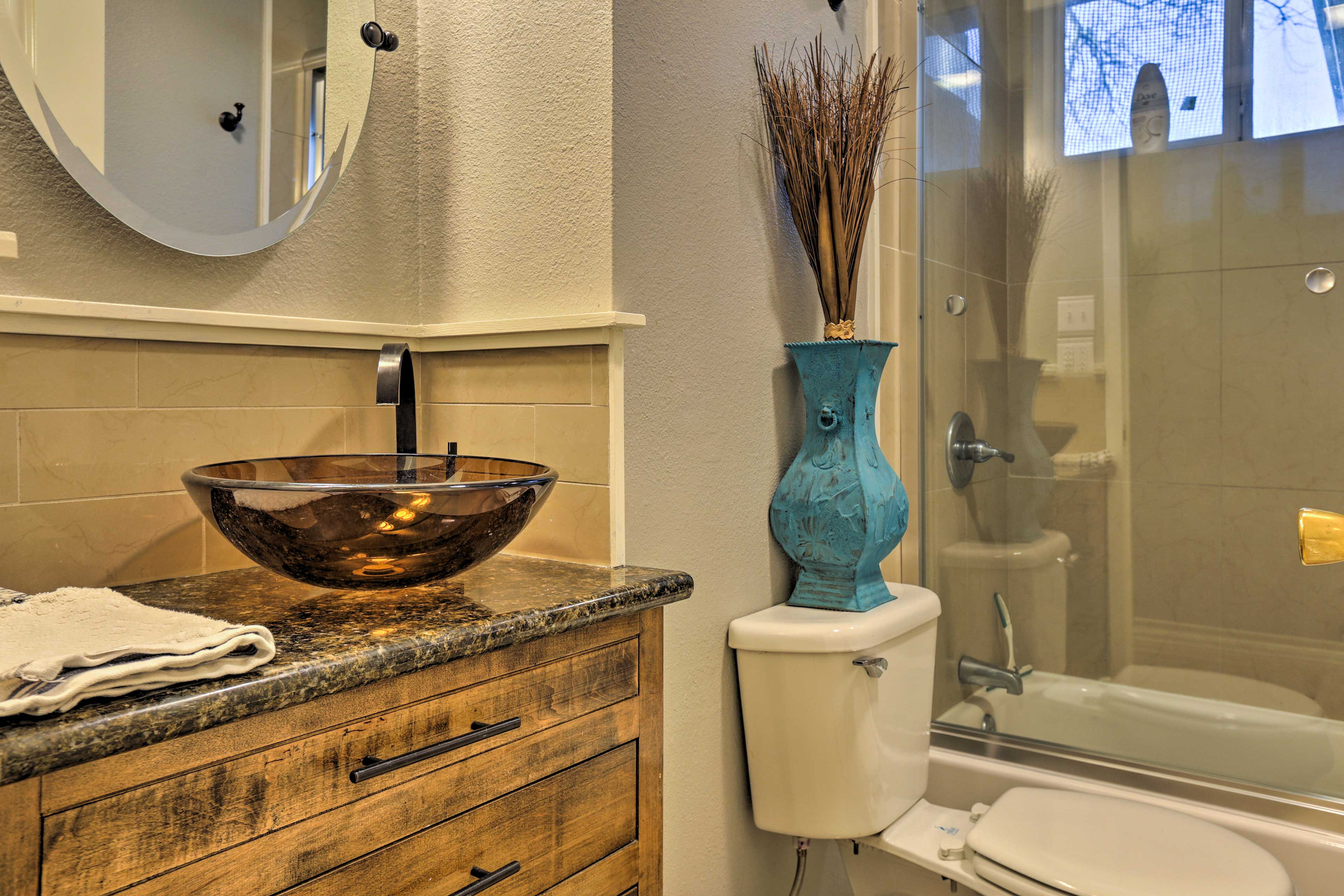 This spotless bathroom houses a vessel sink and tub/shower combo.