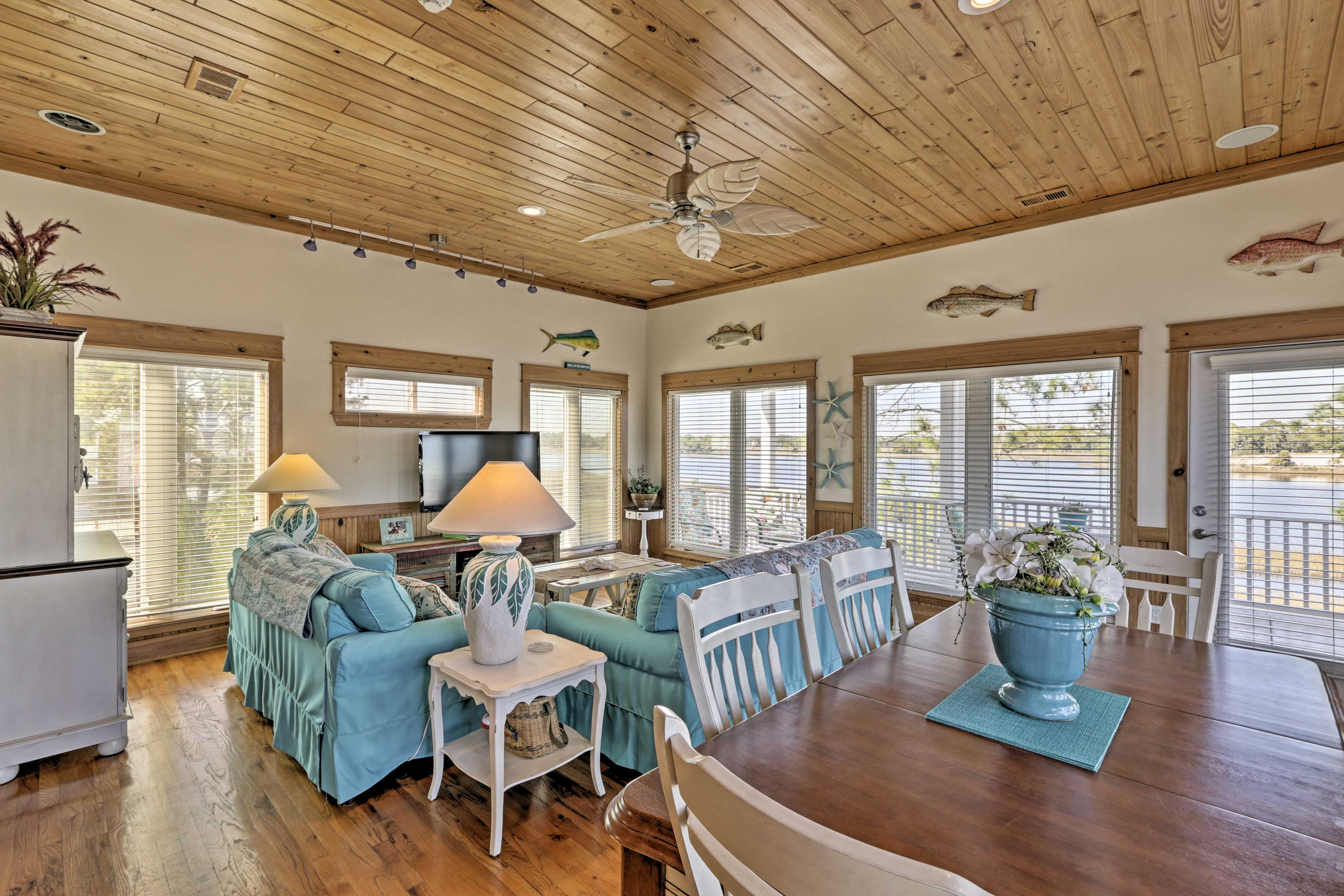 Hardwood floors and ceilings coupled with beach-themed accents elevate this home