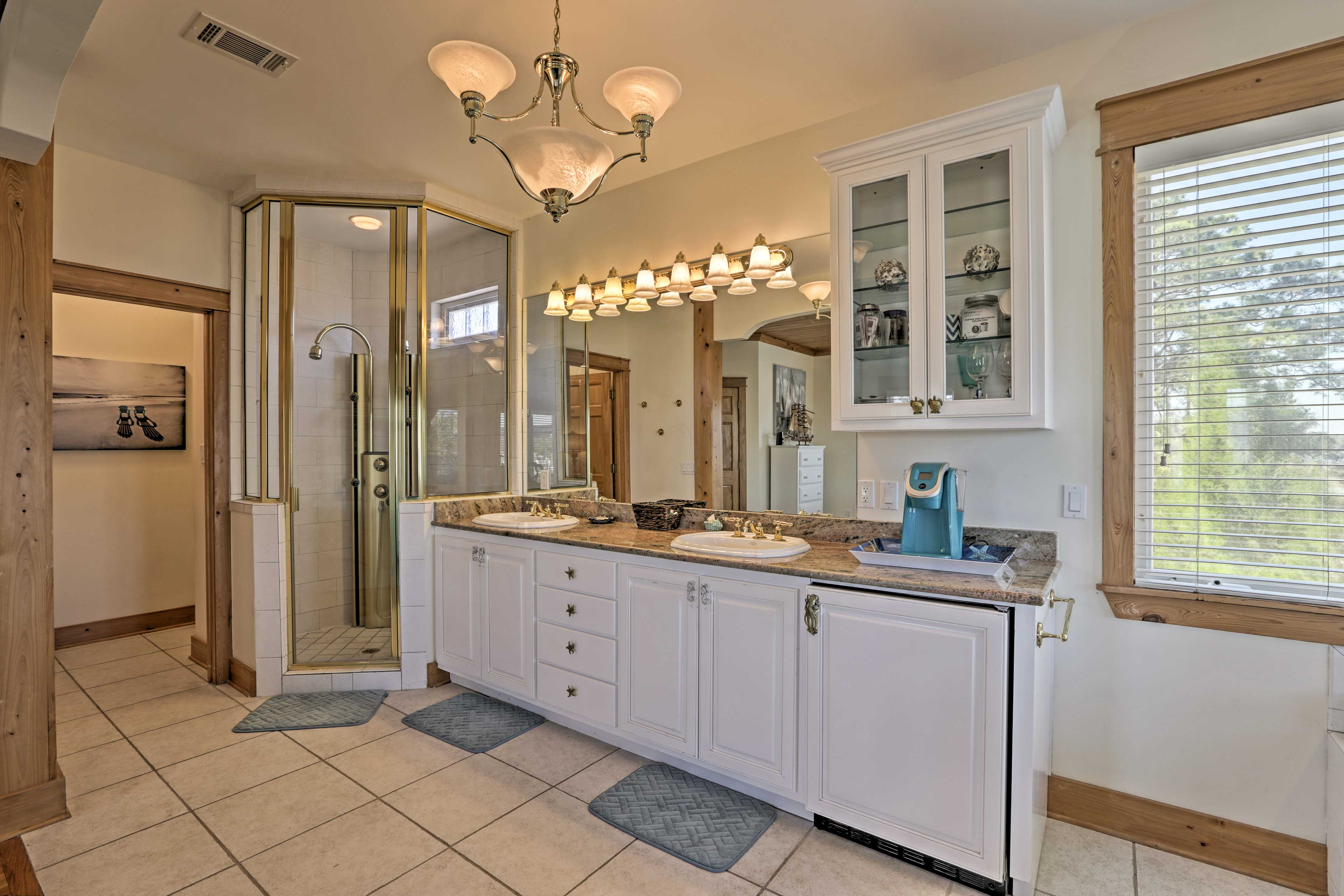This huge en-suite bathroom boasts a walk-in shower, spacious double vanity,  jetted tub and mini fridge.