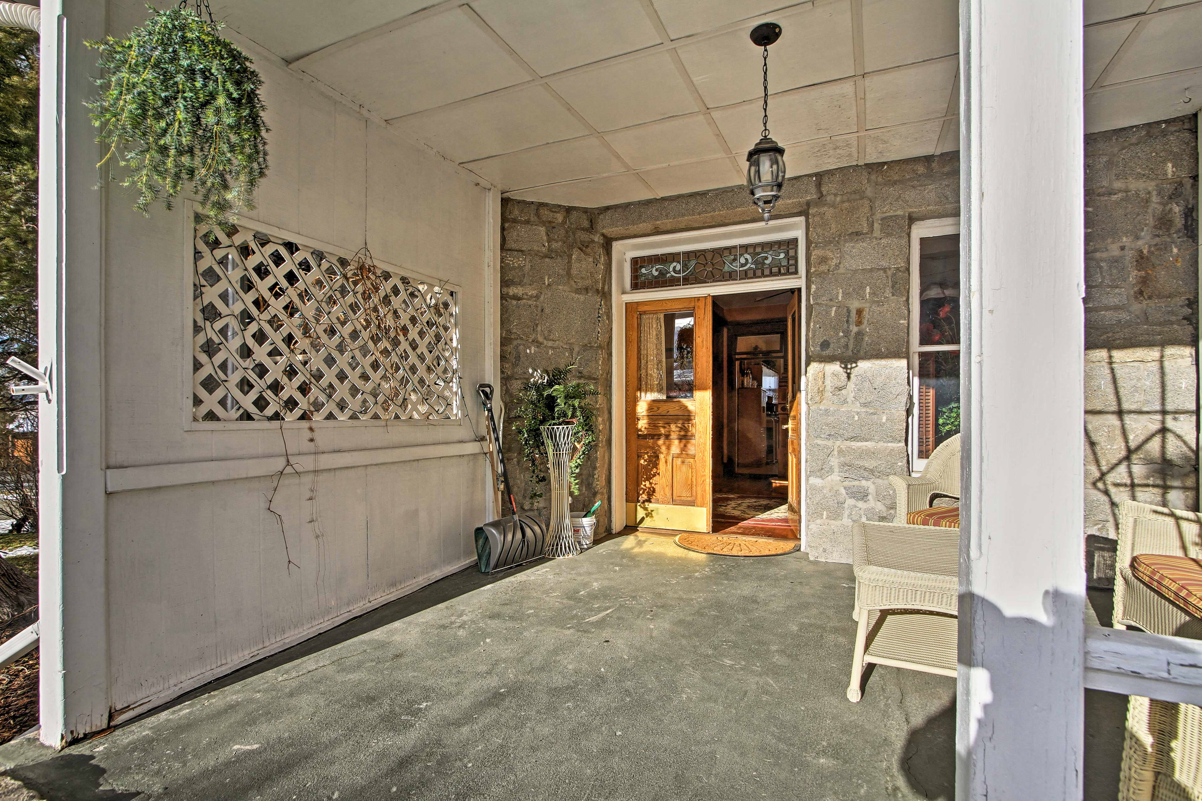 Upon arrival, you'll be welcomed by the home's cozy furnished porch.