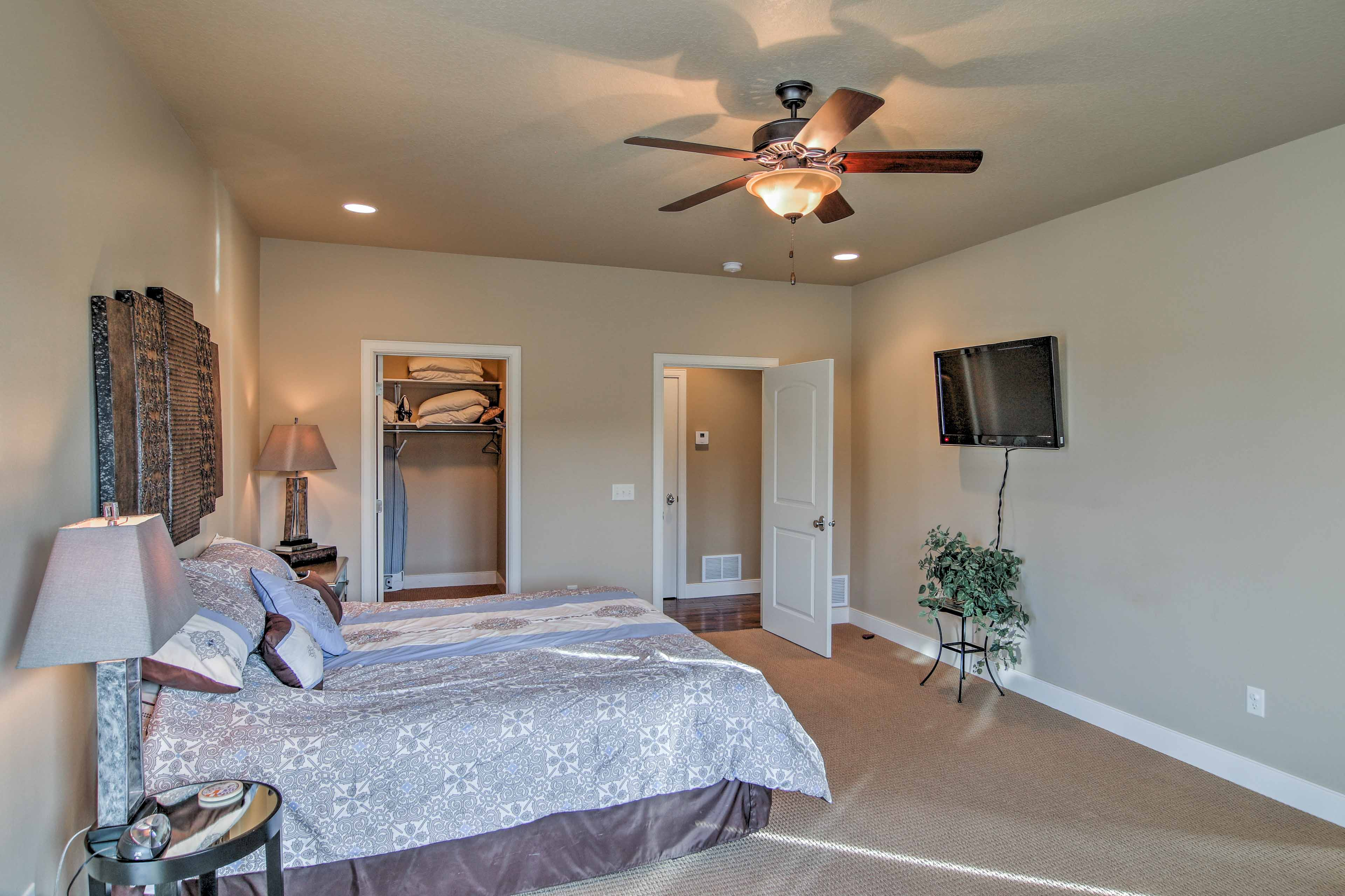 The master bedroom features a flat-screen TV, pullout couch, and balcony access.