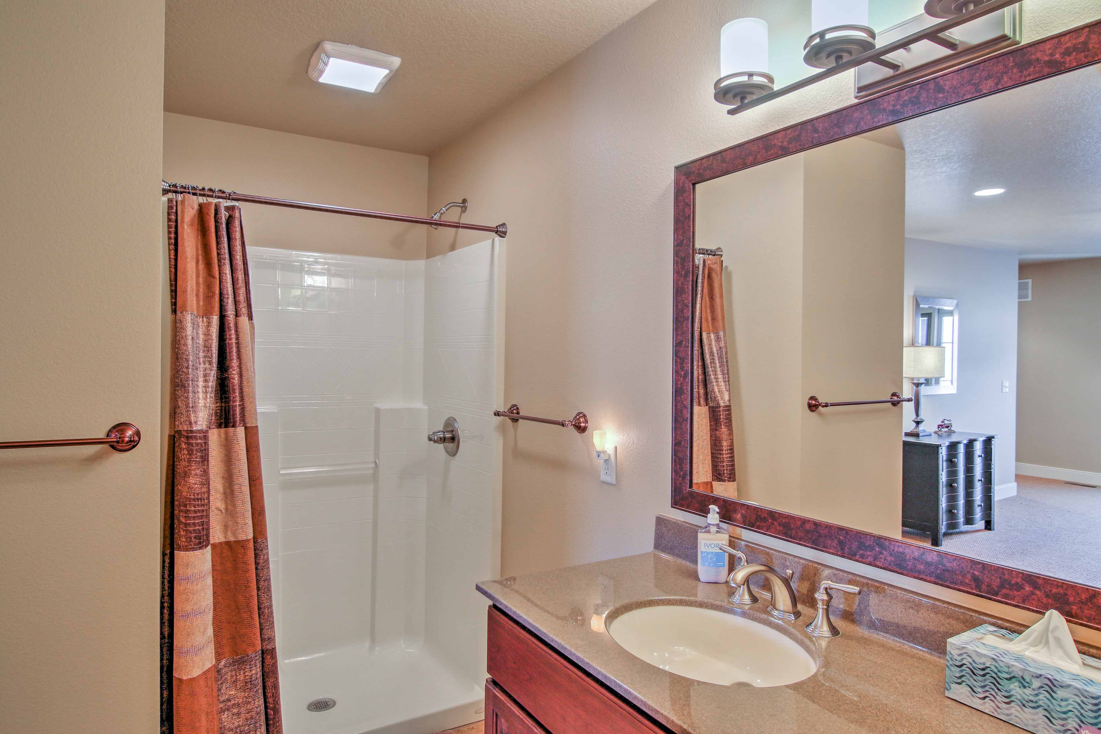 This en-suite bathroom is equipped with a walk-in shower and single vanity.