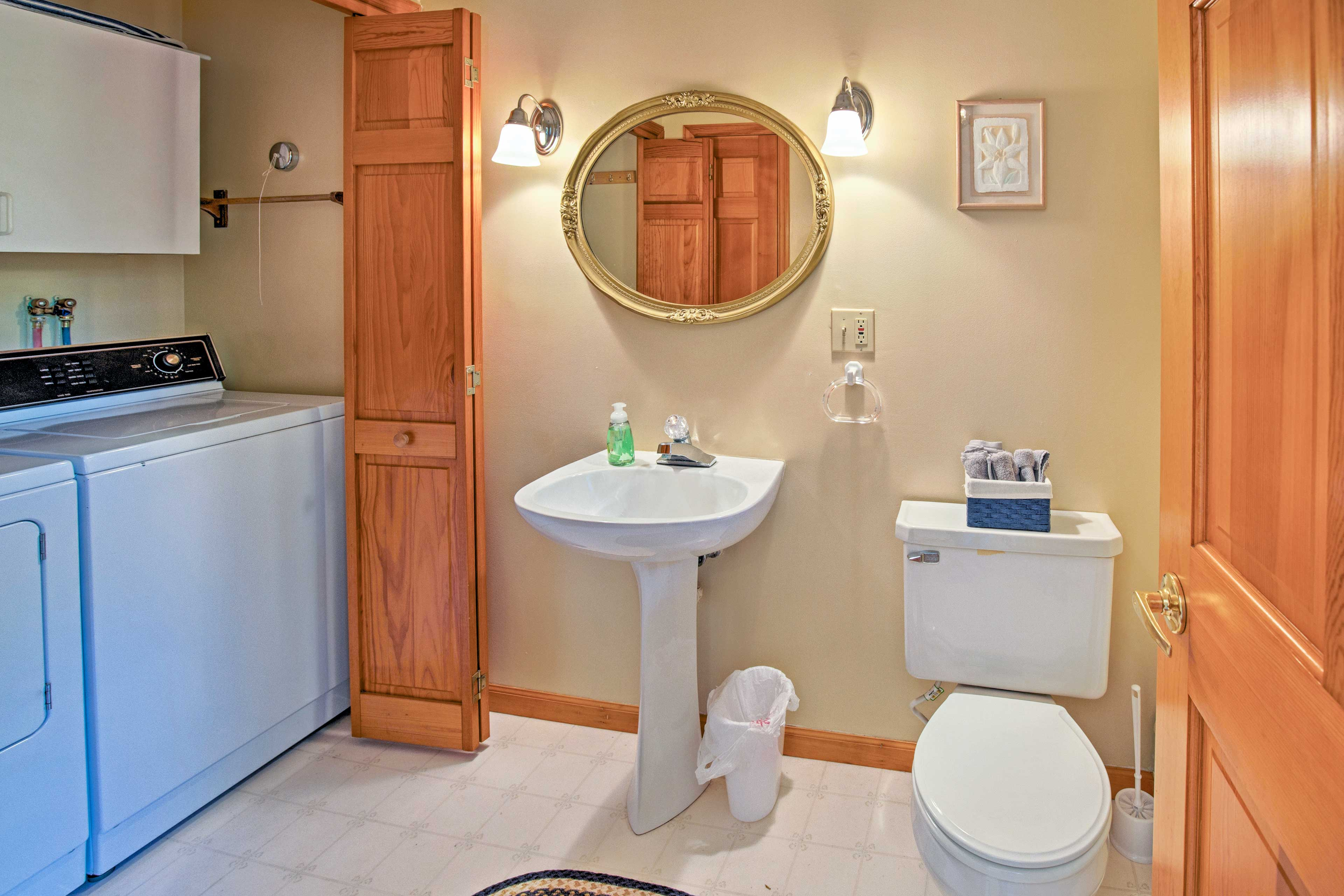This powder room also hosts the in-unit laundry machines.