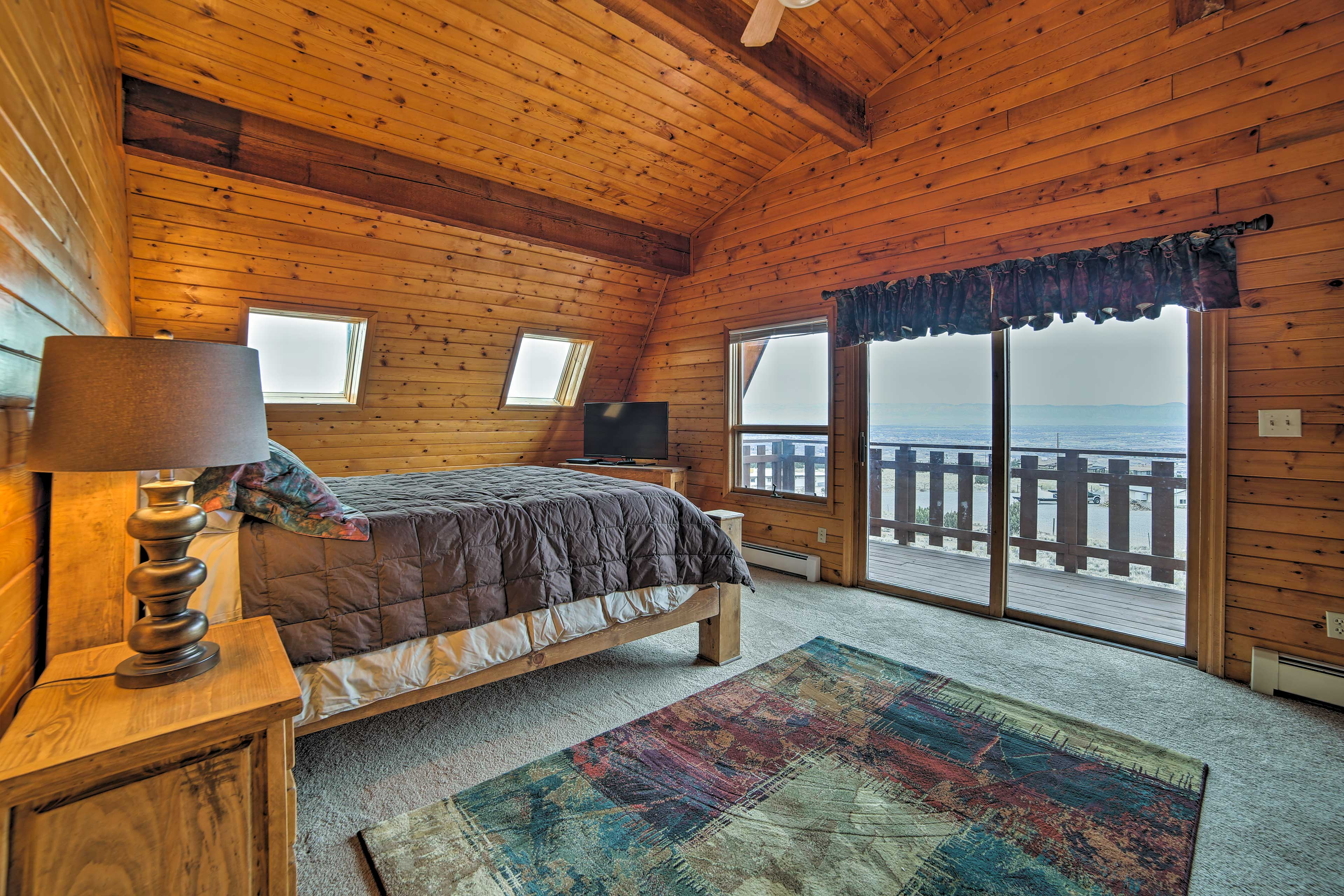 This master bedroom offers vaulted ceilings and access to the second floor deck.
