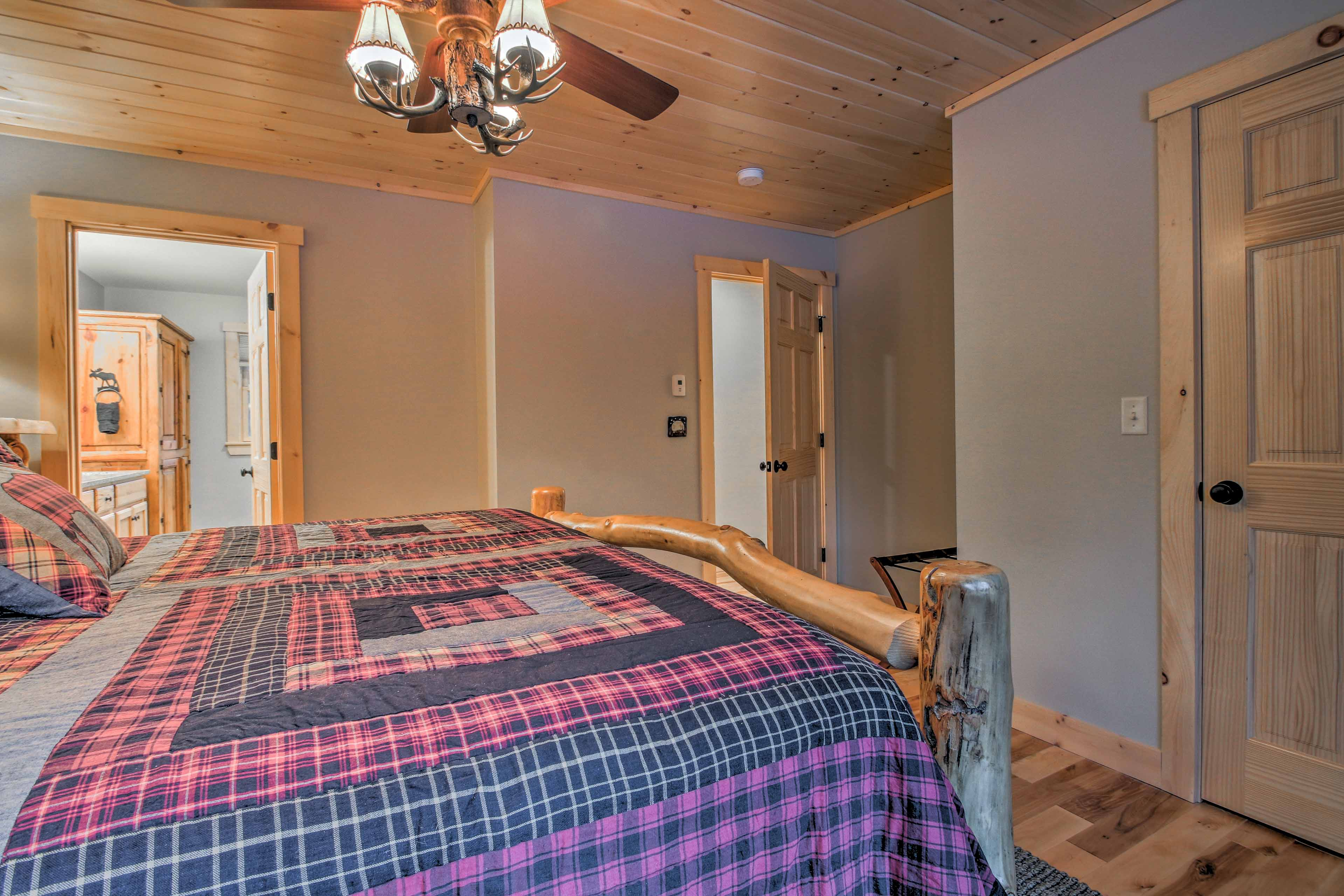 This first master suite features a luxurious king bed with a pine log bed frame.