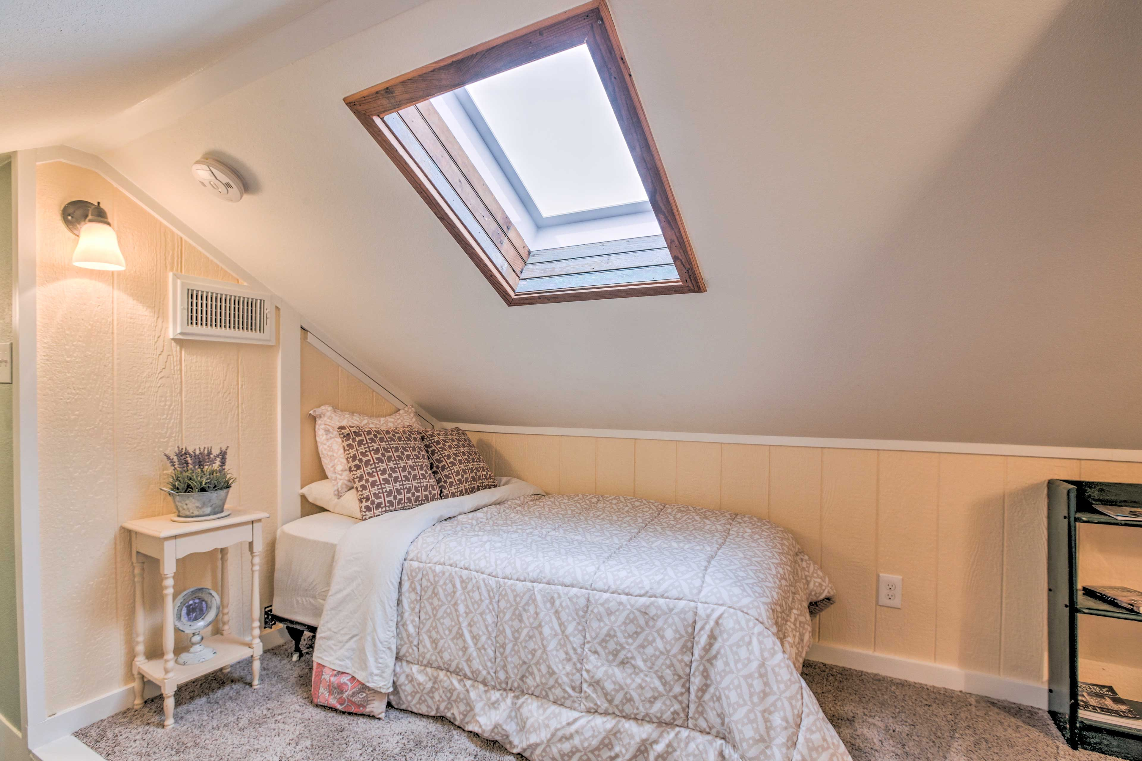 Natural light pours into the upstairs bedroom through the skylight.