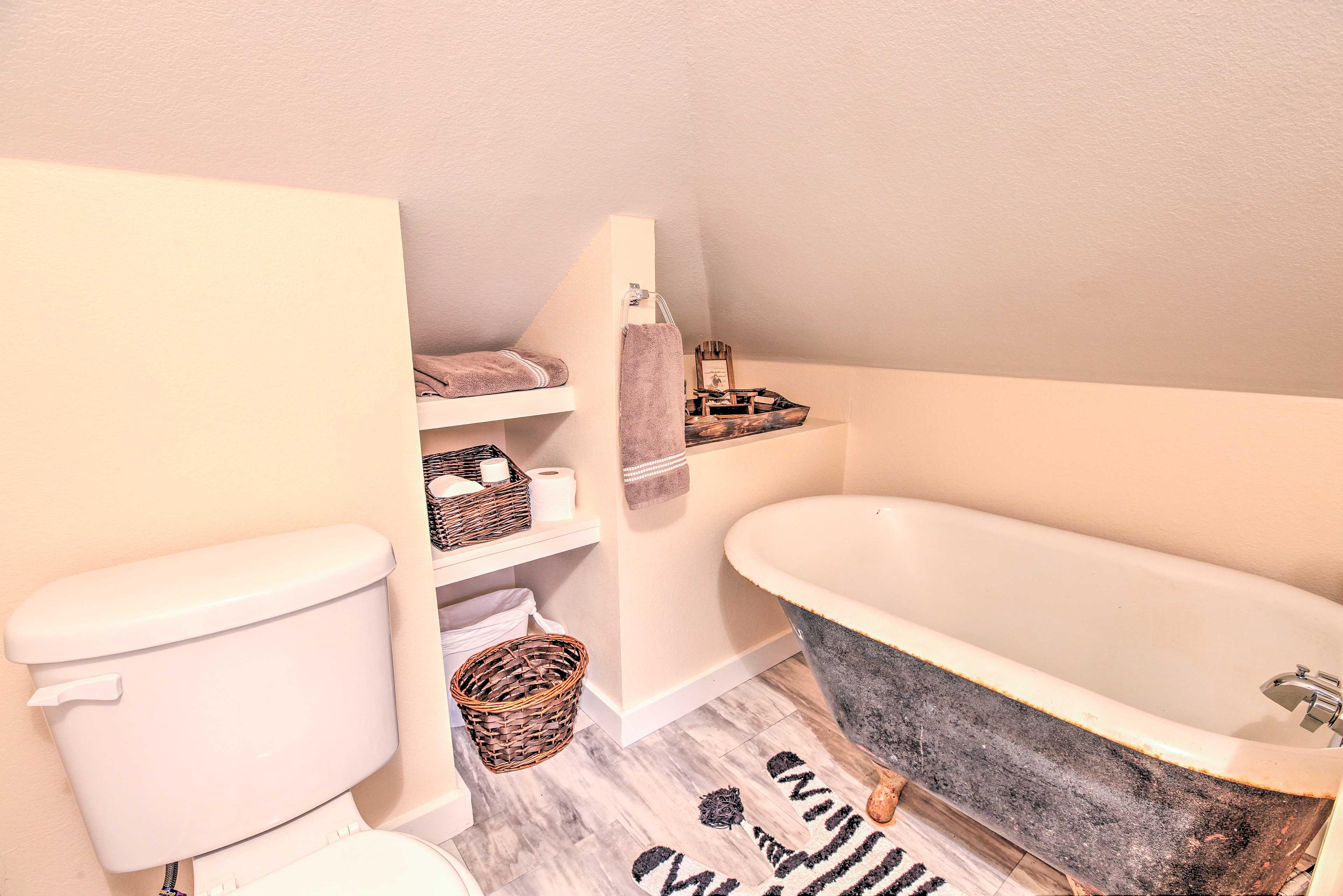The en-suite bathroom offers an antique tub.