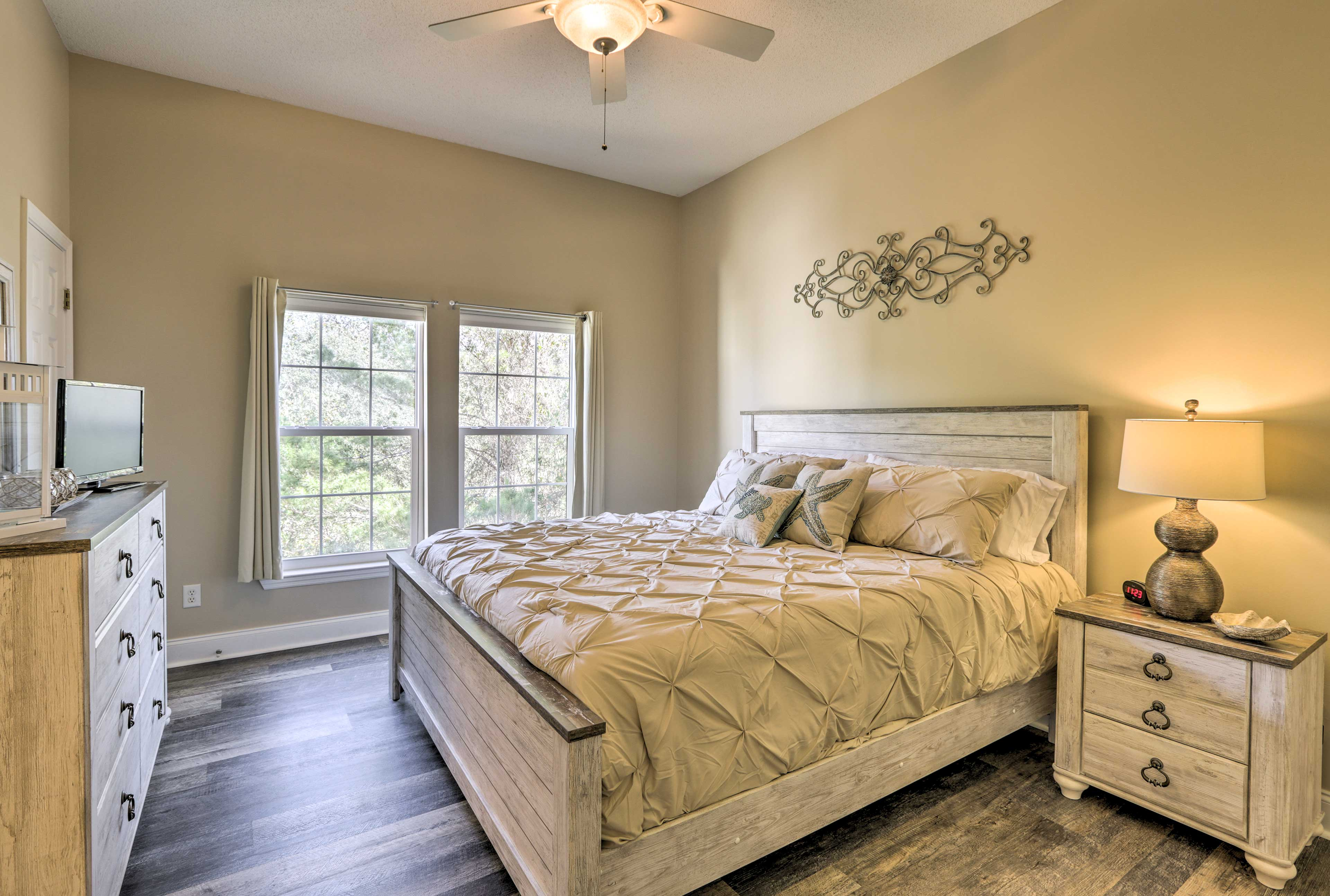 The master bedroom is decorated with elegant taupe, white, and khaki decor.