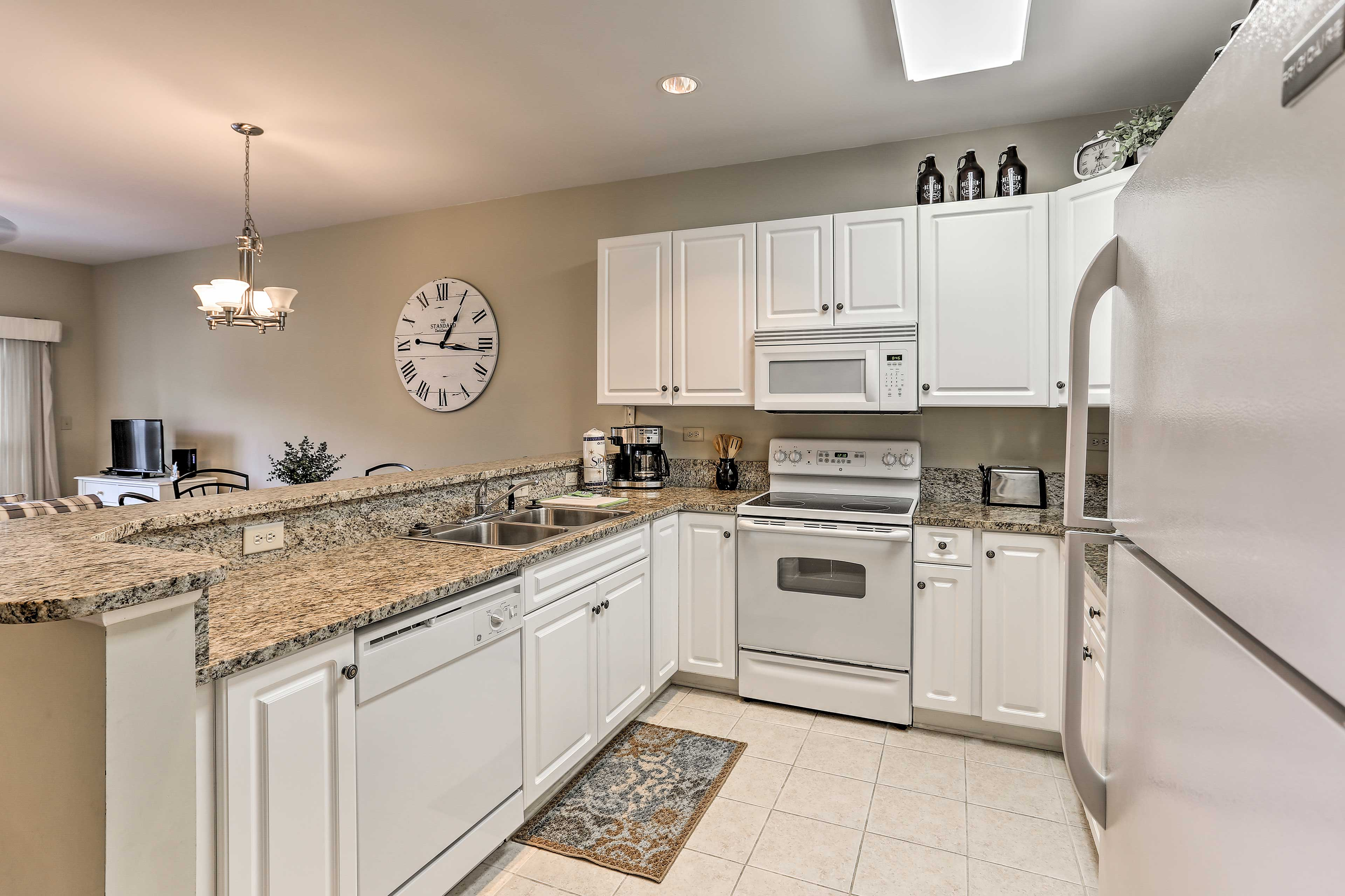 The fully equipped kitchen features granite countertops and timeless shaker-style cabinetry.