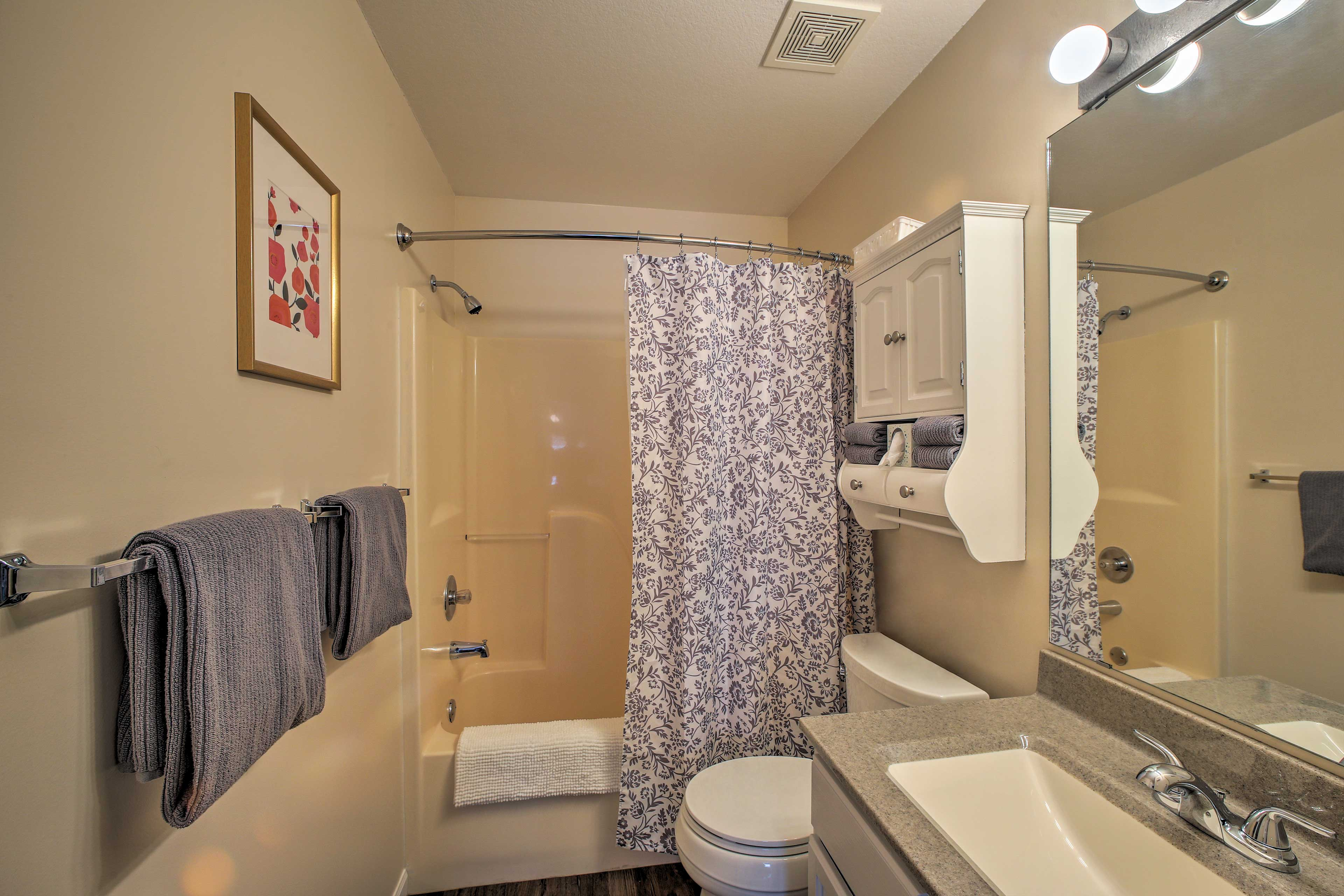 Freshen up in the master bathroom, with a shower/tub combo.