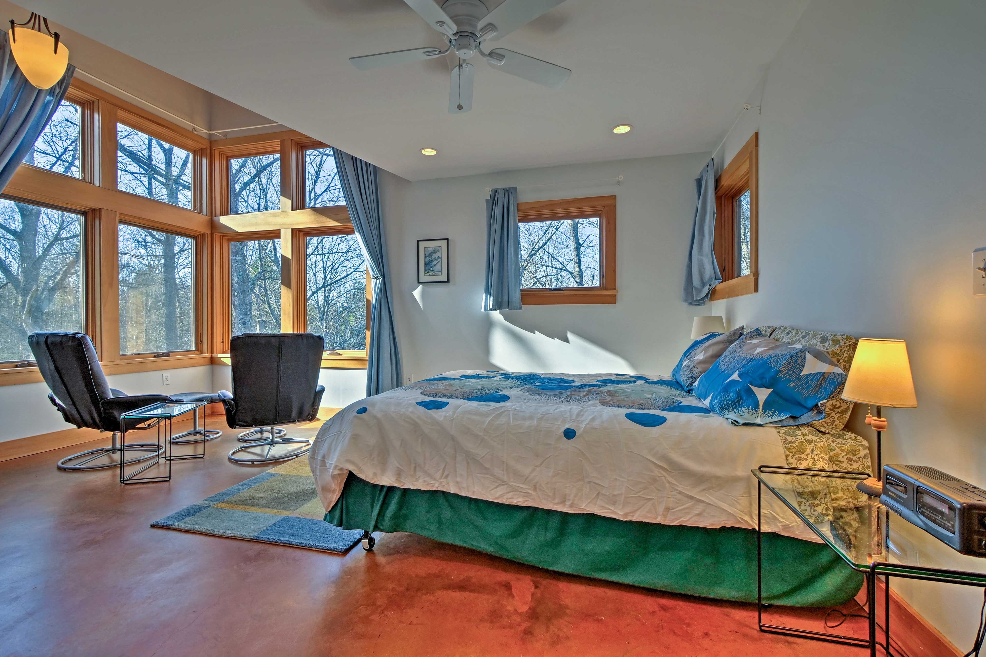 The master bedroom features breathtaking natural views and a plush king bed.