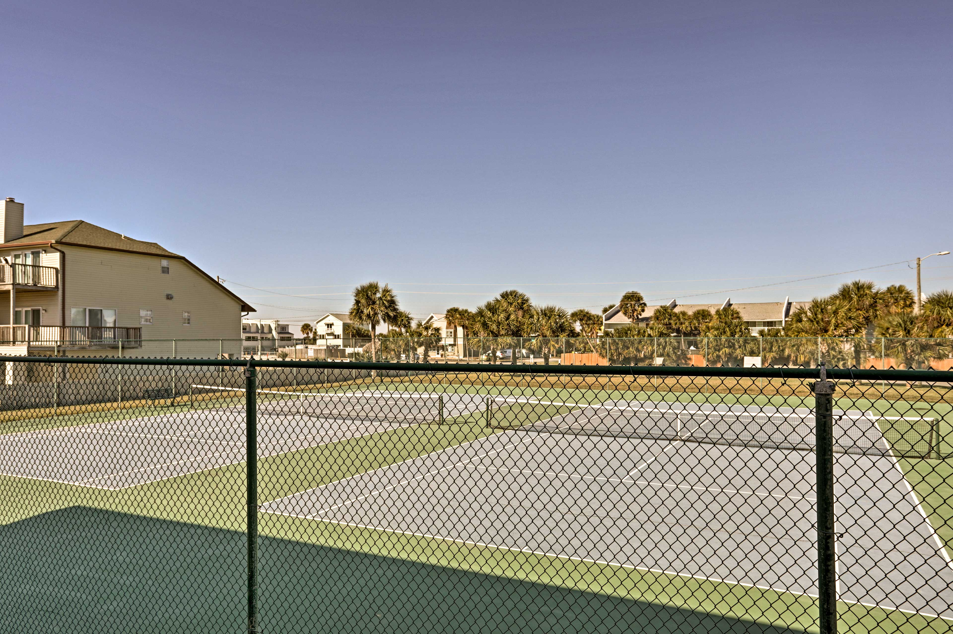 The complex includes a tennis court.
