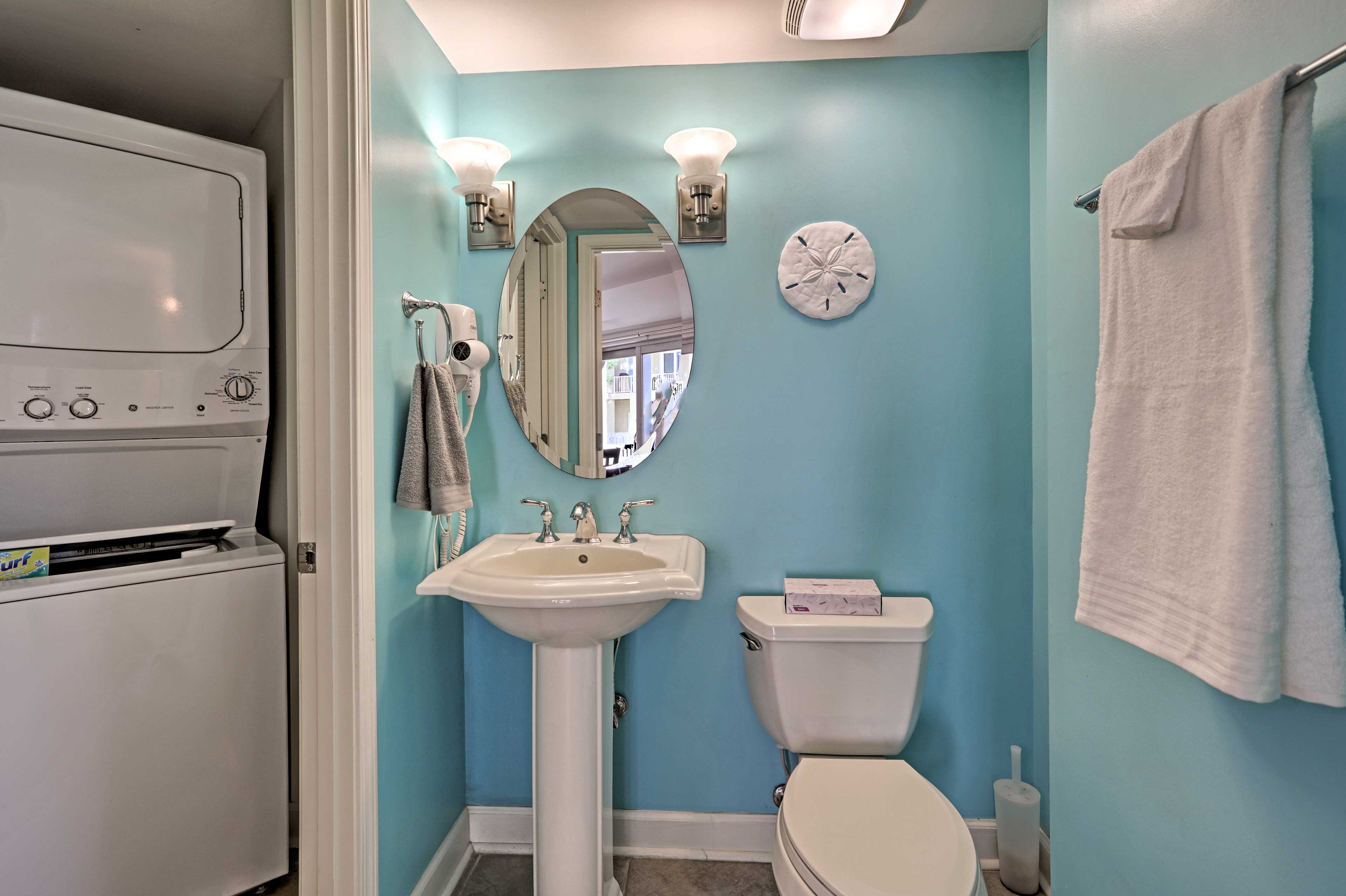 The half-bath is located next to the washer and dryer.