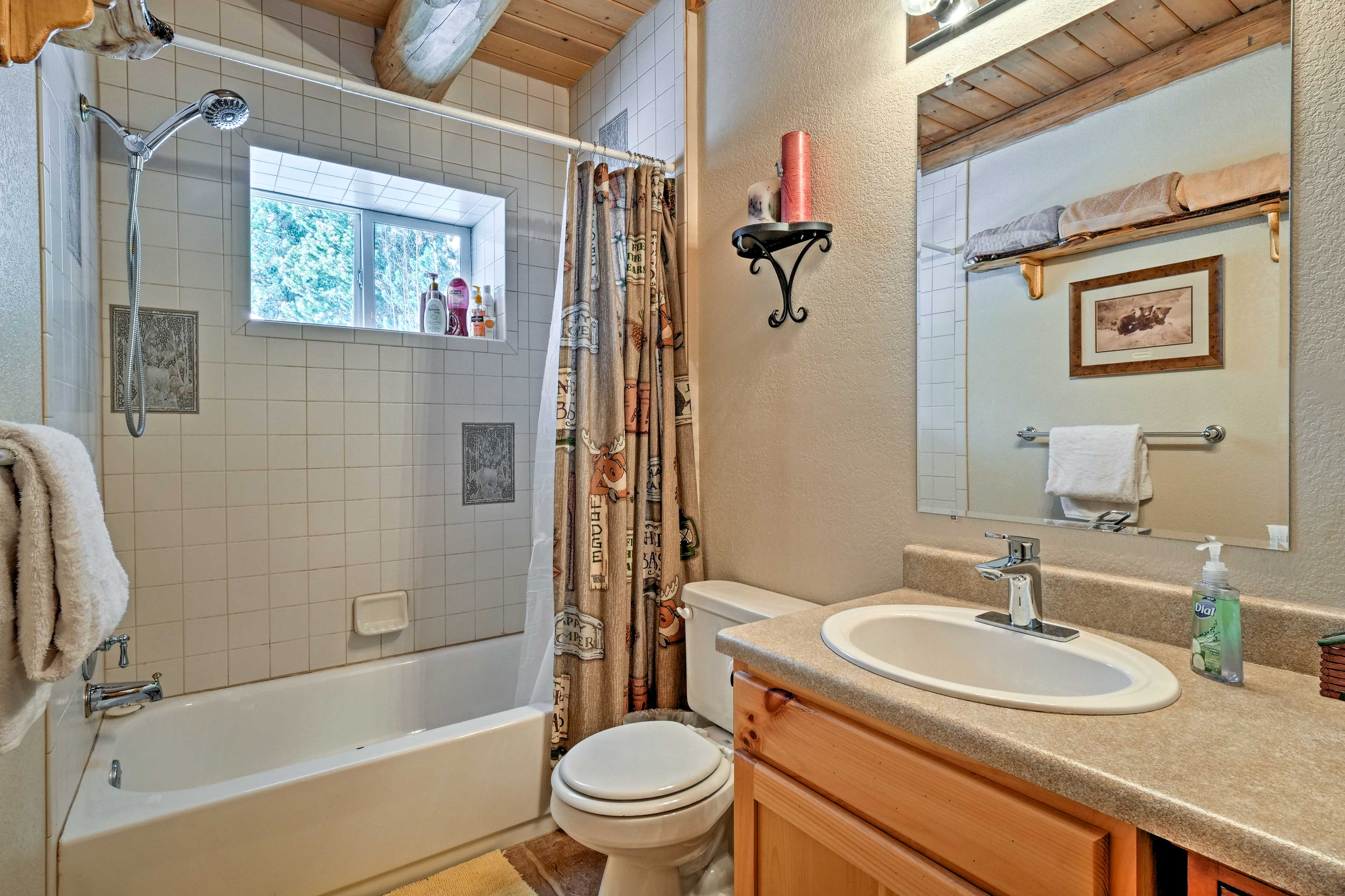 The first bathroom is equipped with a single vanity and shower/tub combo.