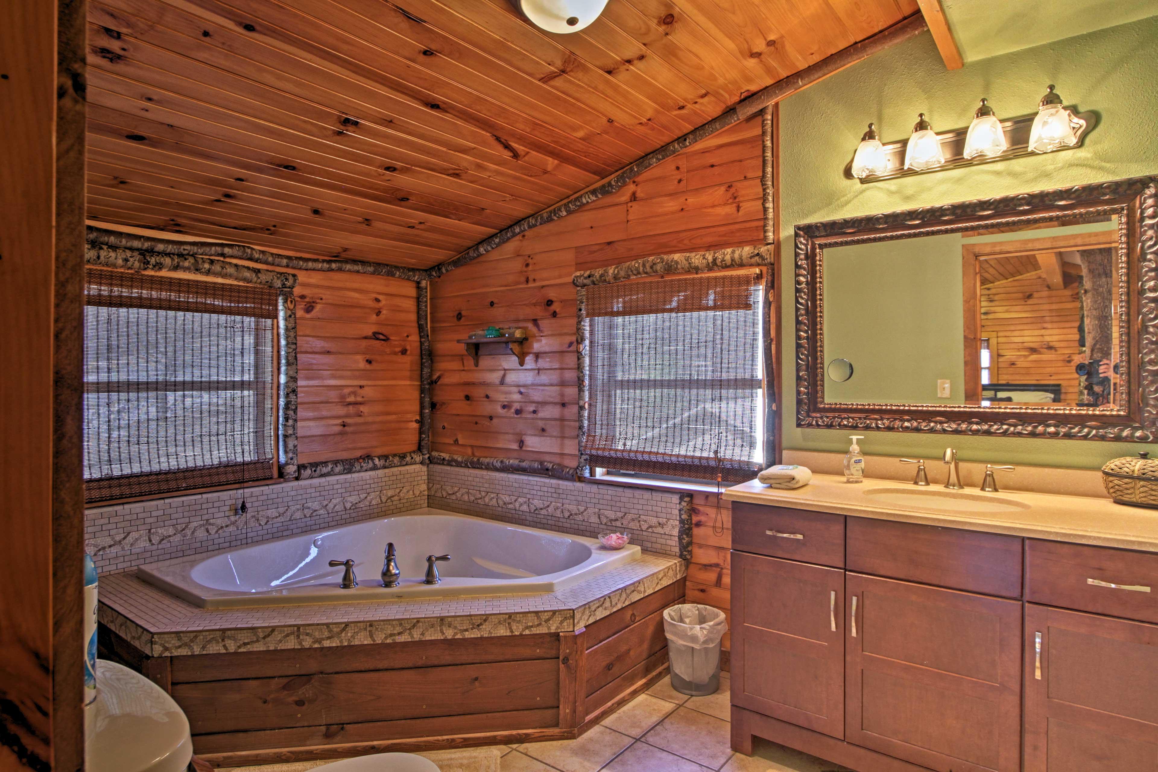 The en-suite bathroom houses a large soaking tub.