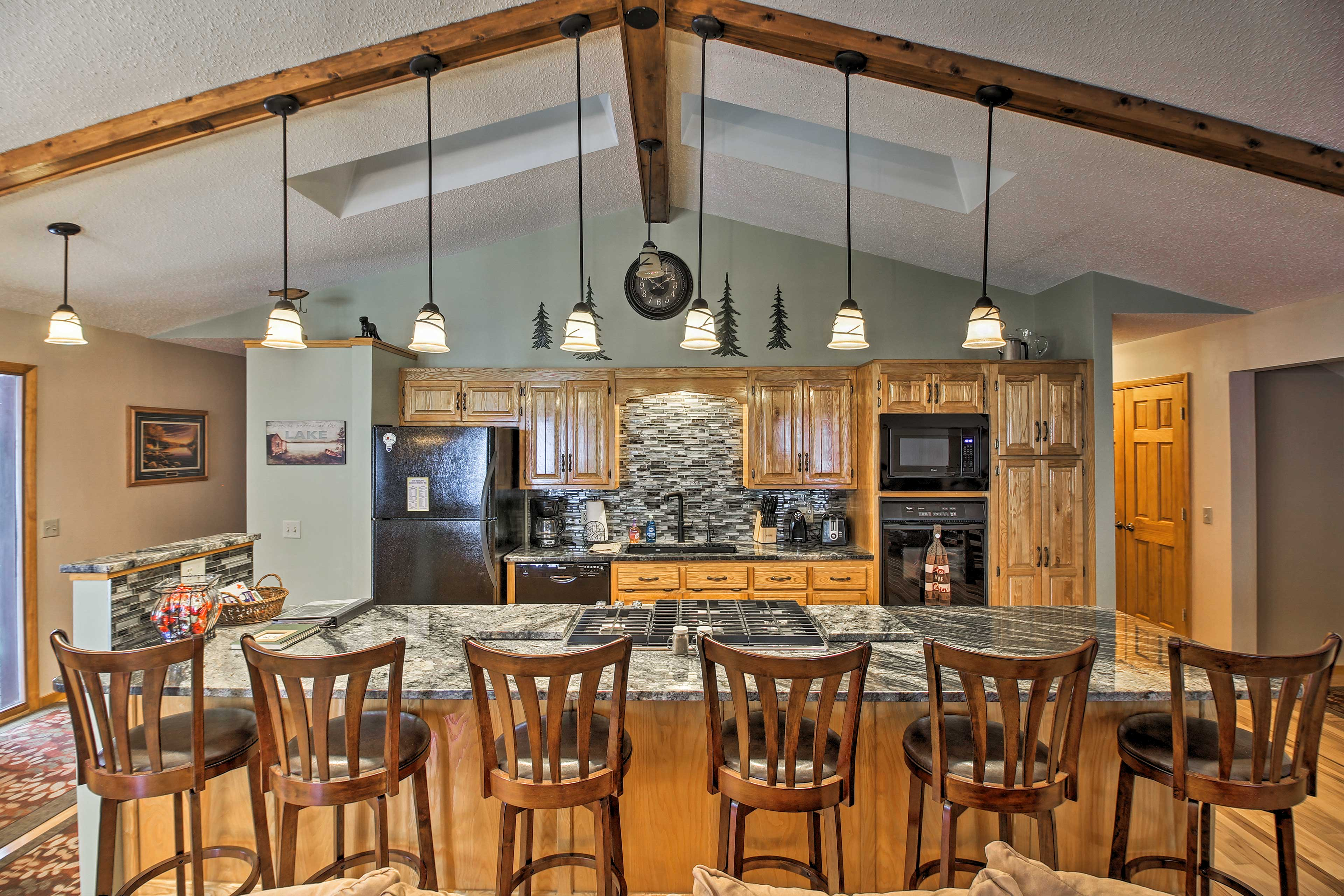 Head to the fully equipped kitchen with granite counters and a large island.