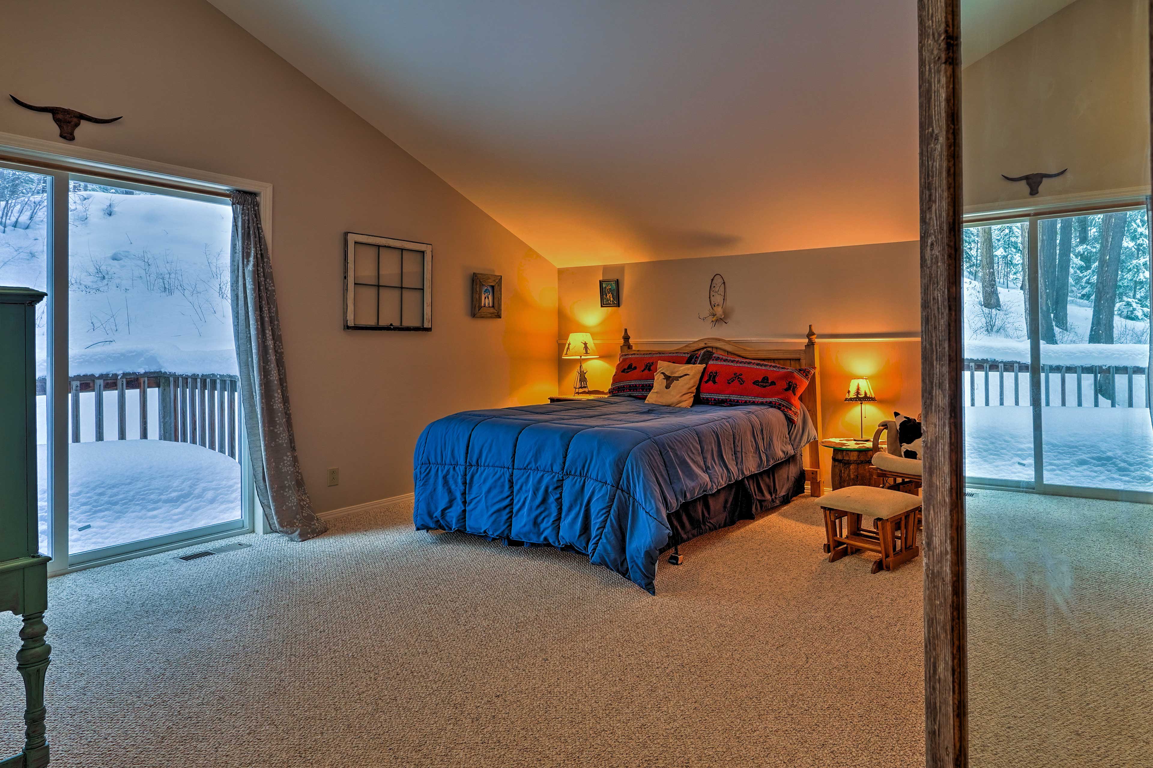 This open and airy bedroom boasts a queen bed and balcony.