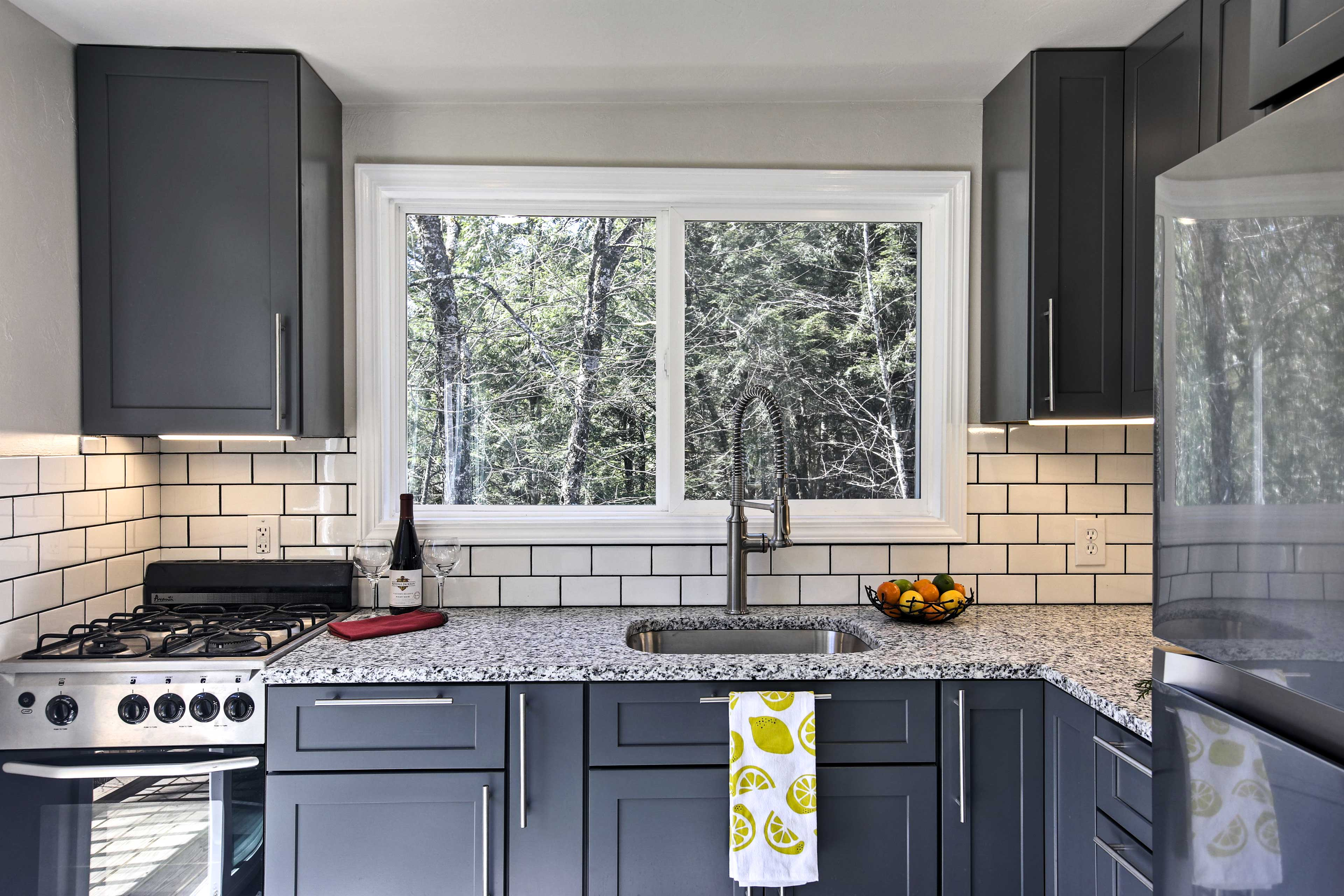 Dark cabinetry complements the sleek white tile in this well-equipped kitchen.