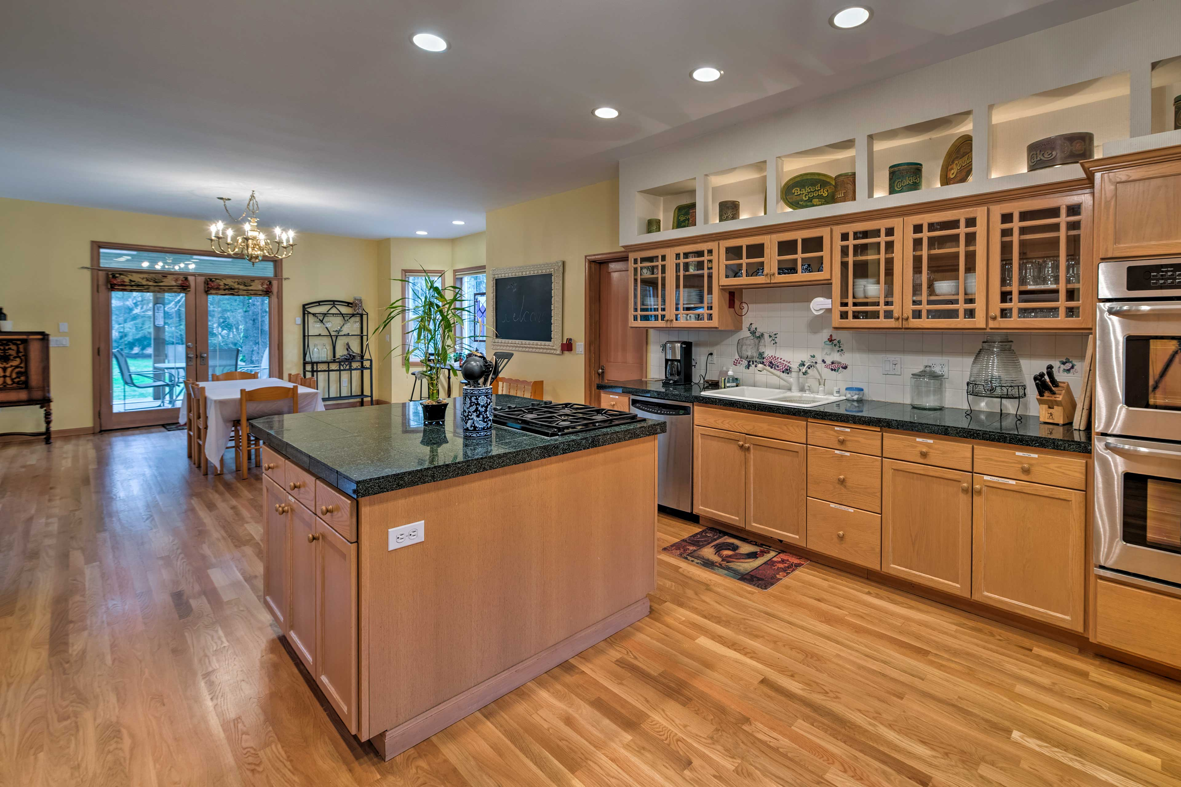 The kitchen has stainless steel appliances, granite counters, and an island.