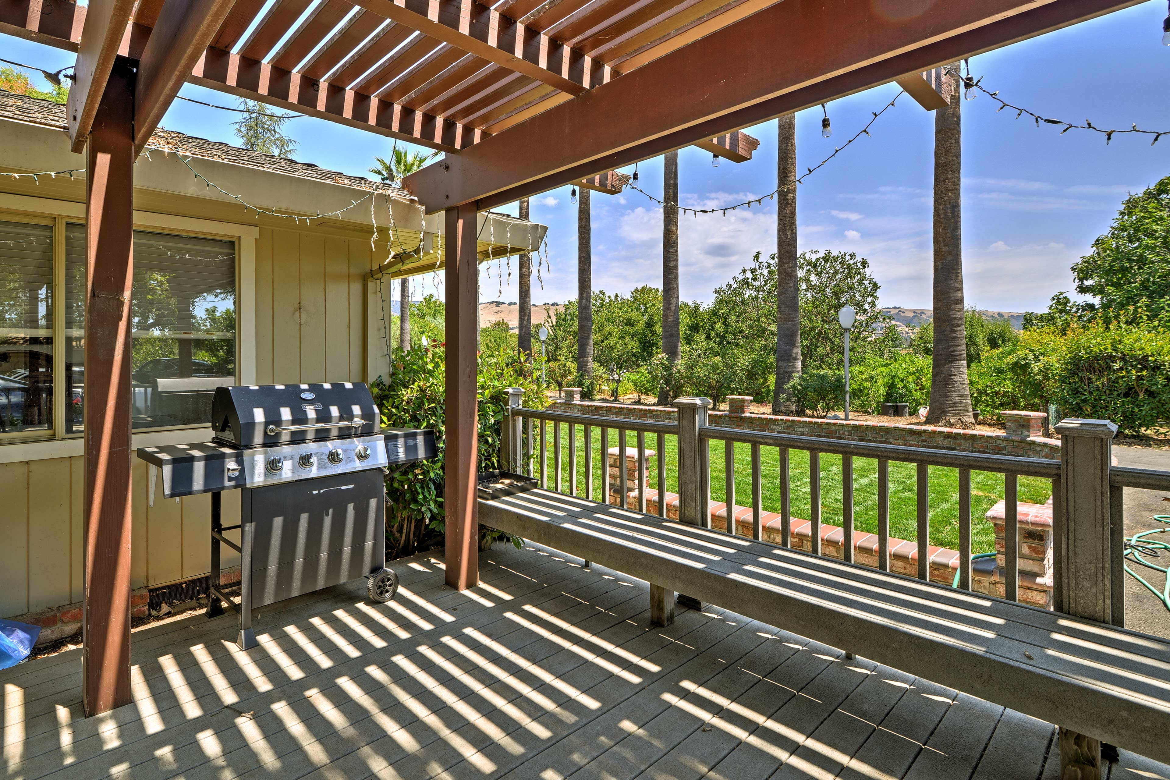 A gas grill, pergola, and bench seating are perfect for an afternoon barbecue.