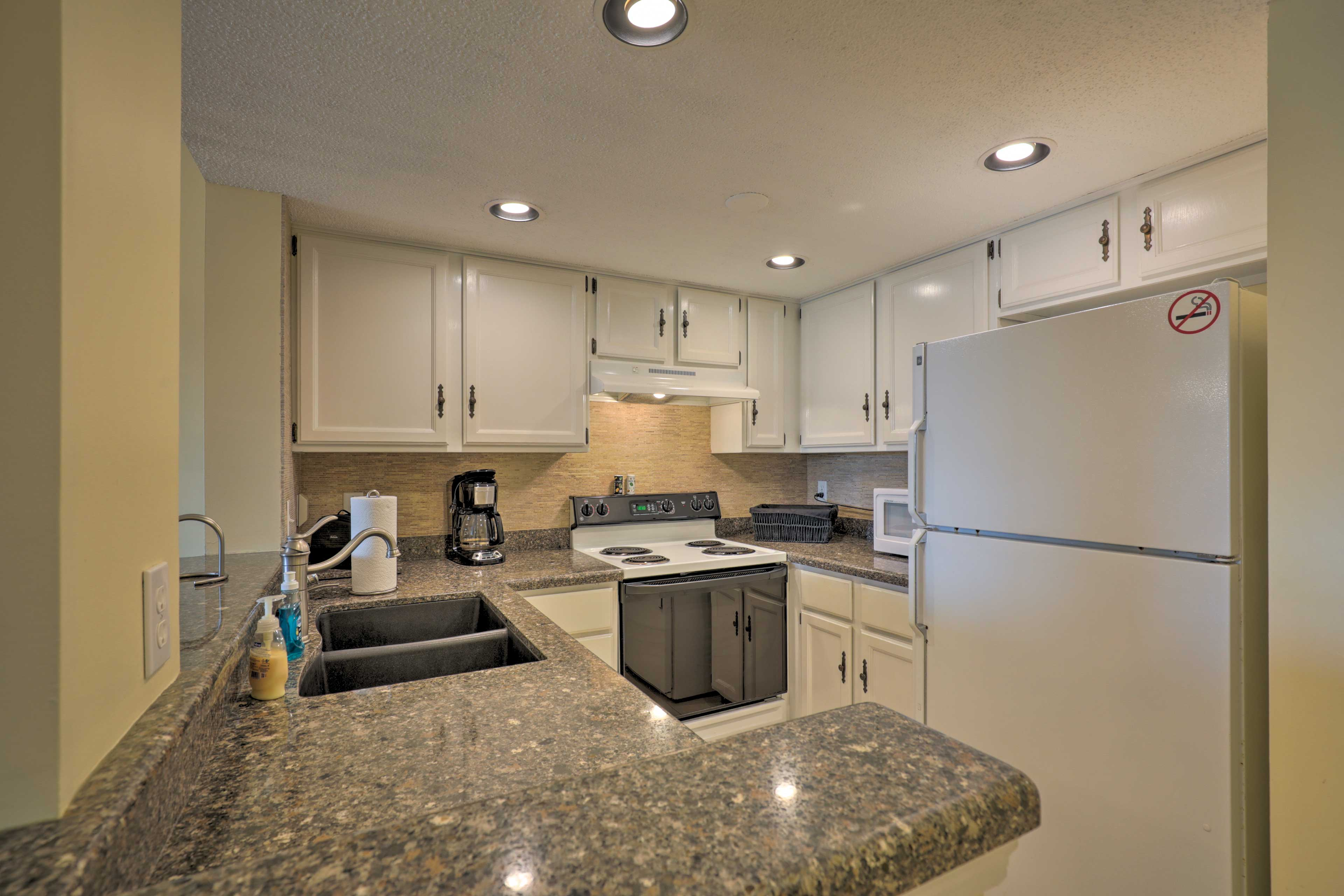 The fully equipped kitchen features modern appliances and granite countertops.