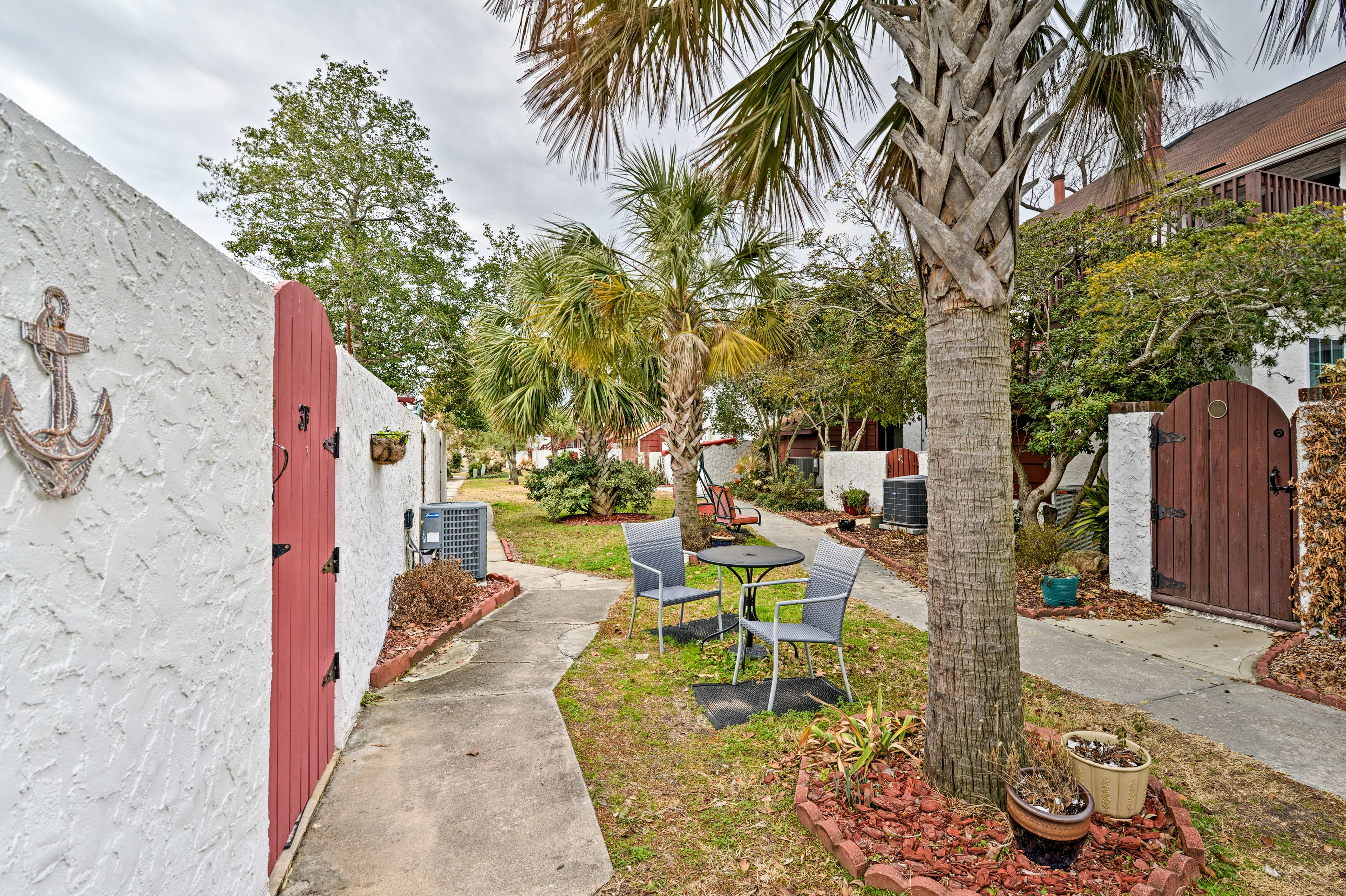 Palm trees lead the way to this charming home.