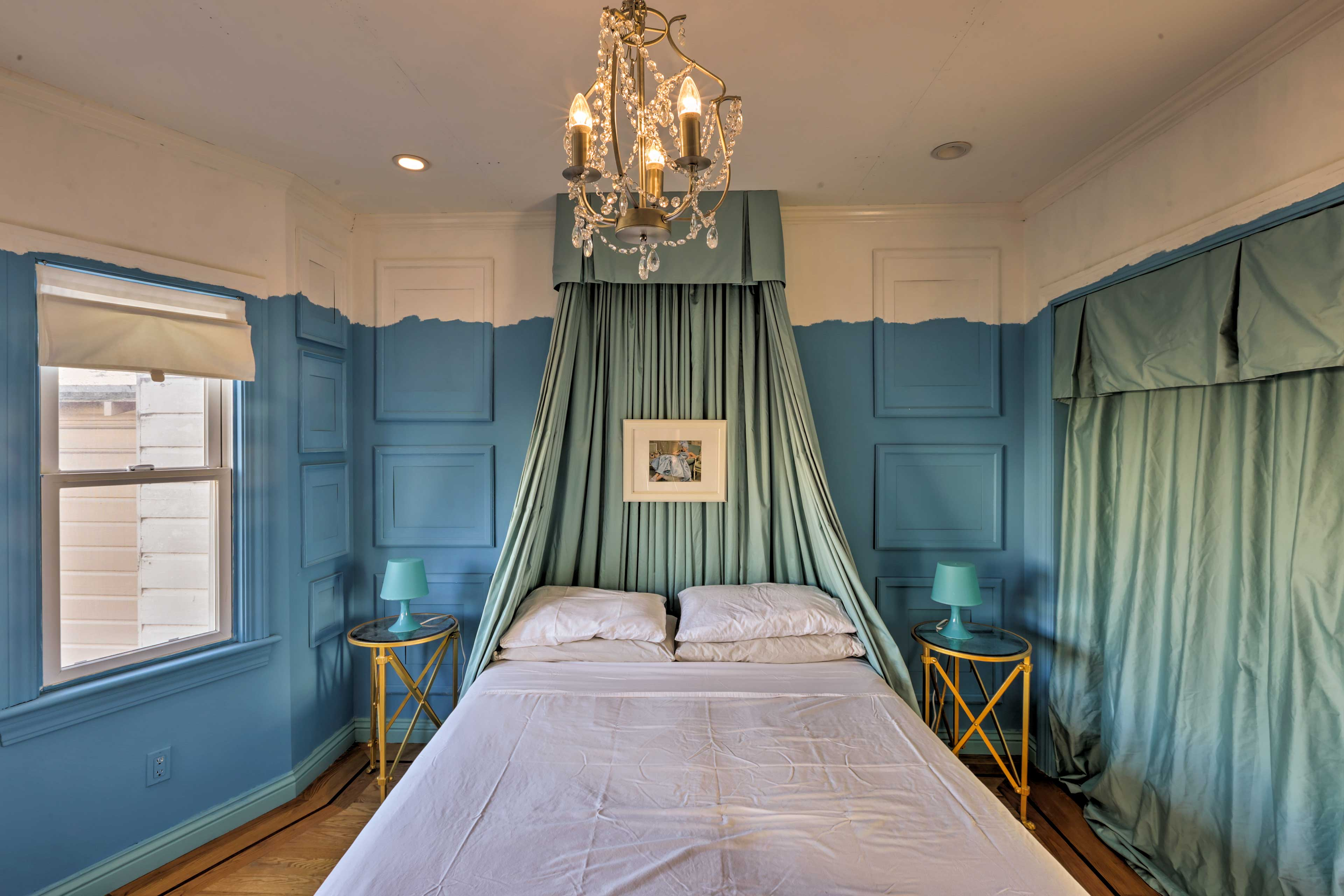 The second bedroom is adorned with blue hues and a curtained headboard.