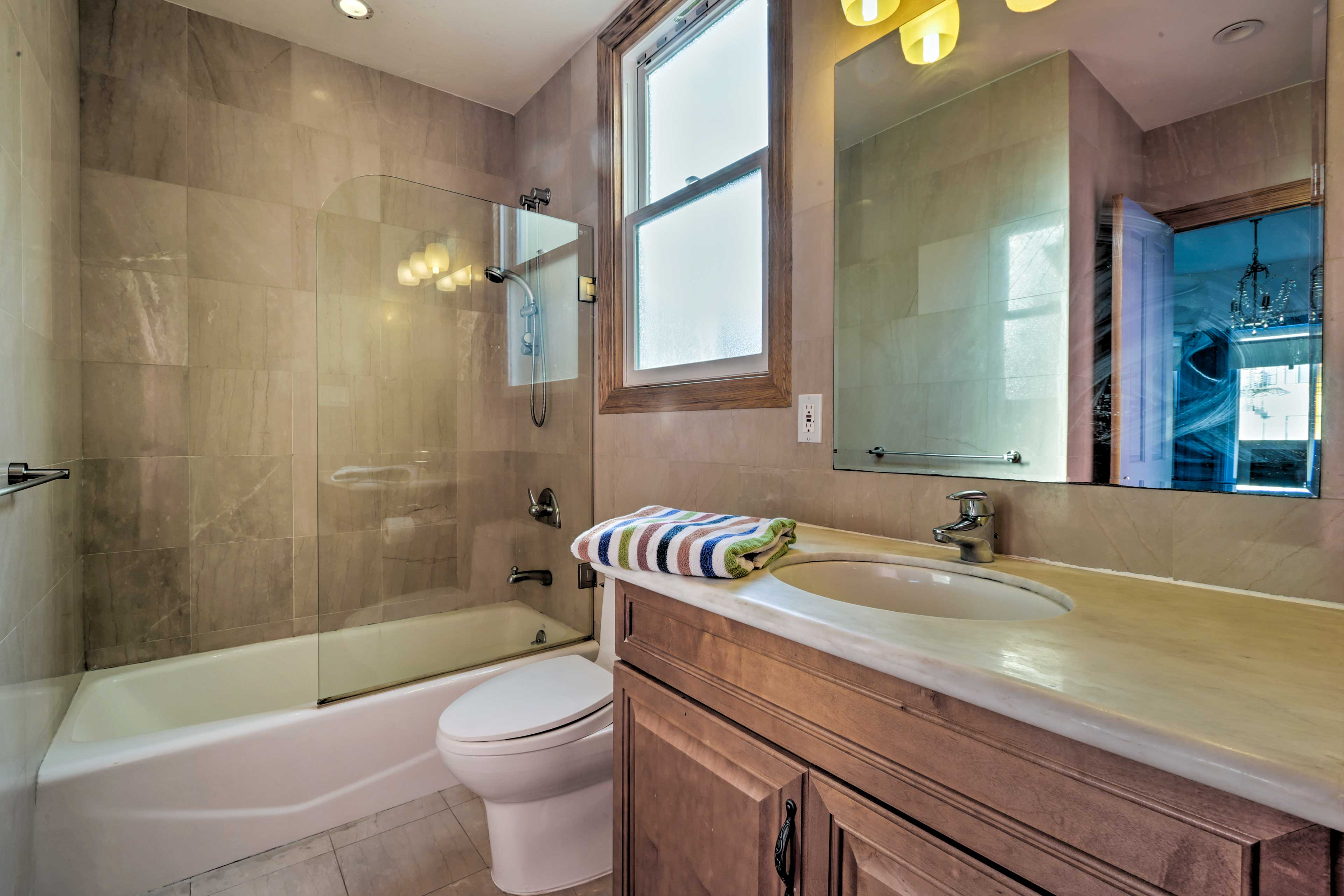 Rinse off in the tub/shower combo, complete with a glass door and marble tiling.