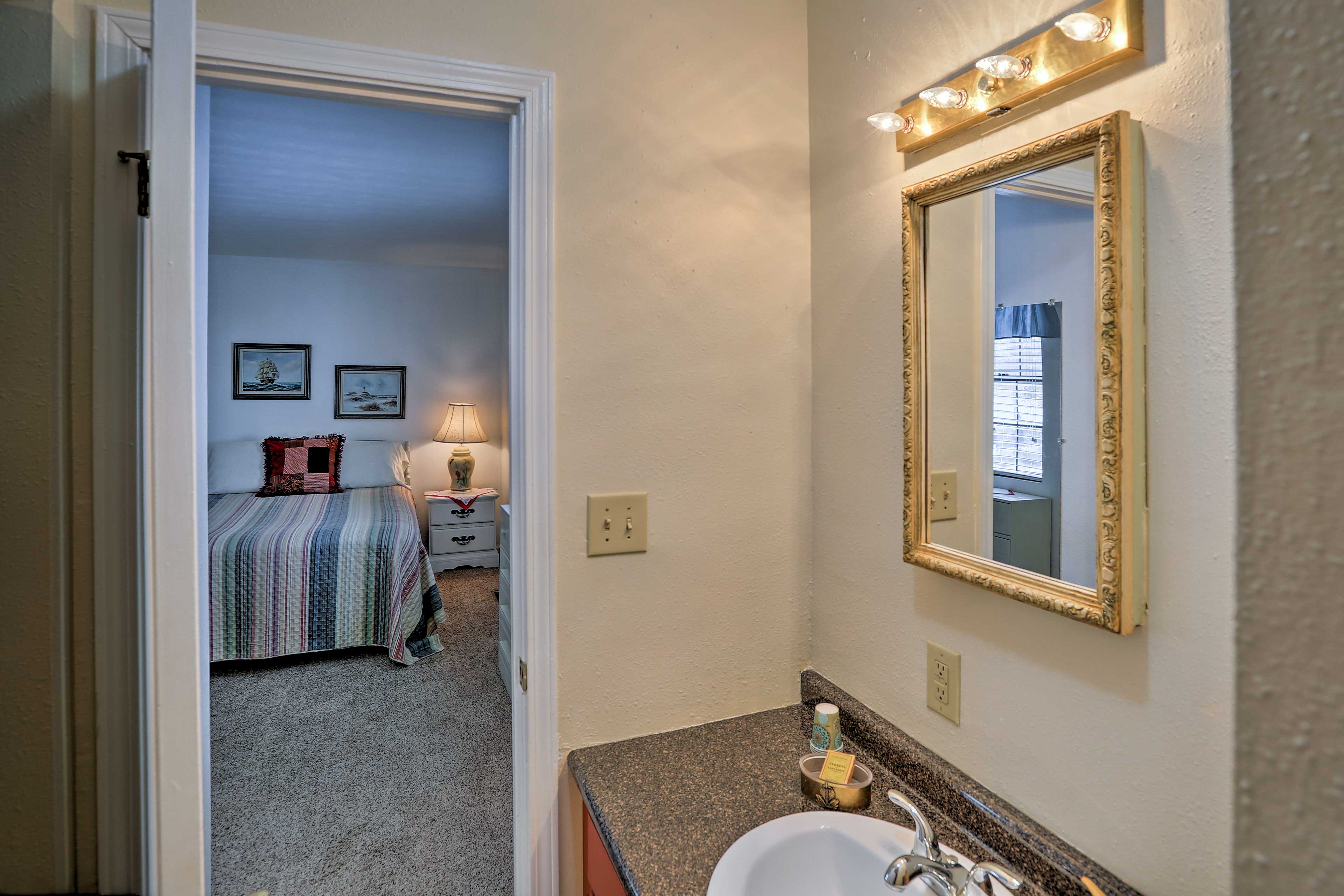 The full bathroom has a single sink, vanity mirror, and a stand-up shower.