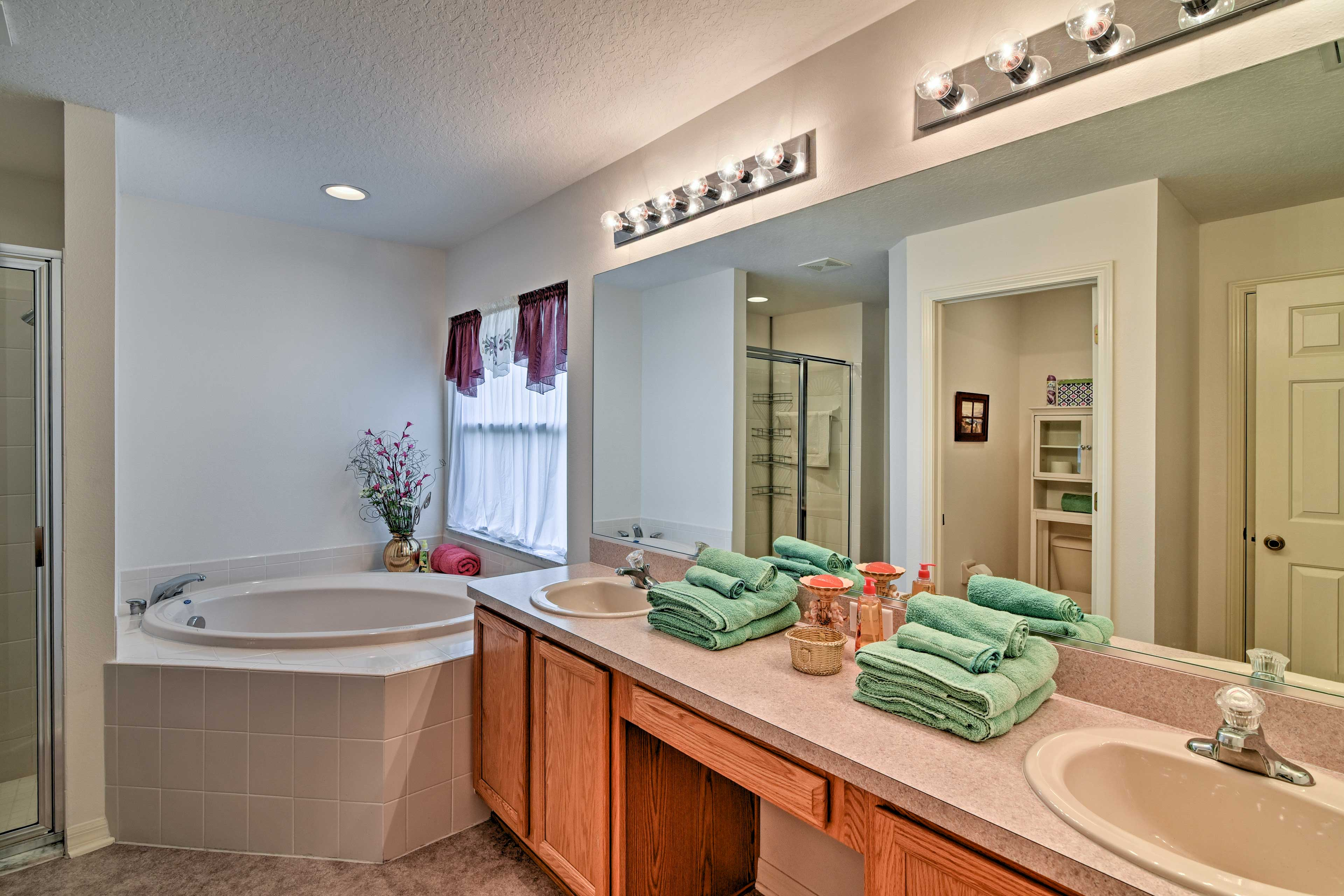 This en-suite bathroom offers a garden tub and a walk-in shower.
