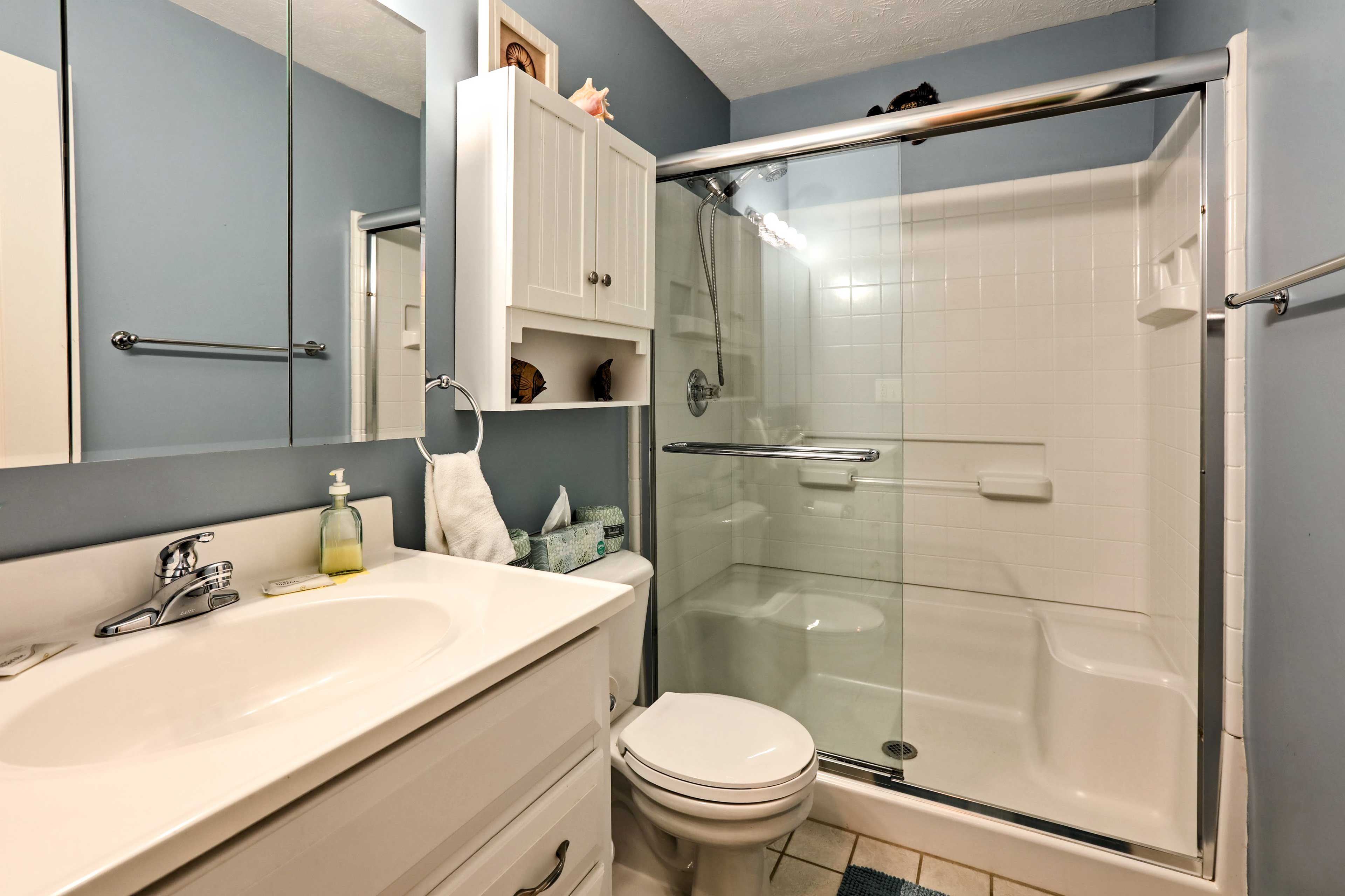 The second bathroom sports a walk-in shower and soft baby-blue walls.