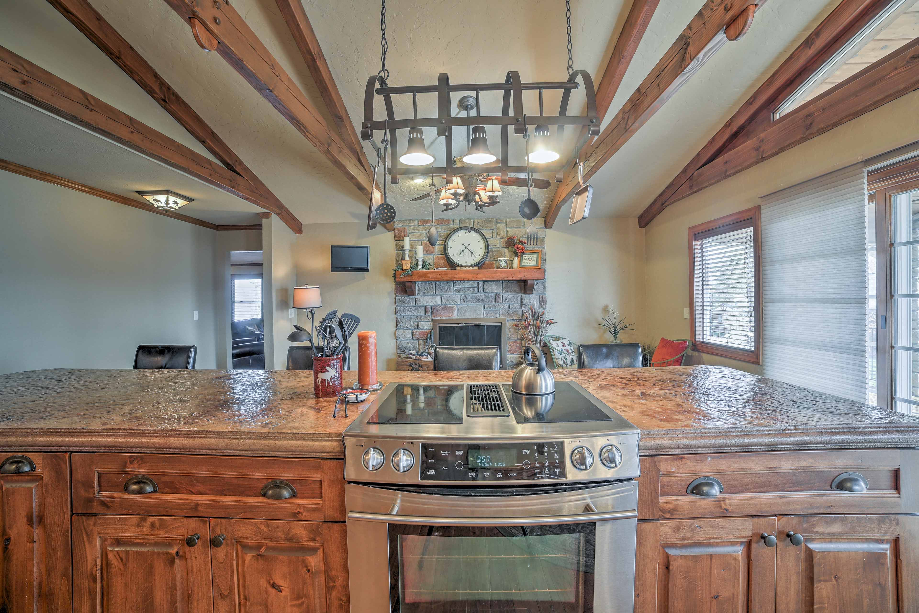 Prepare dinner on the stainless steel stove, lit by a rustic chandelier.
