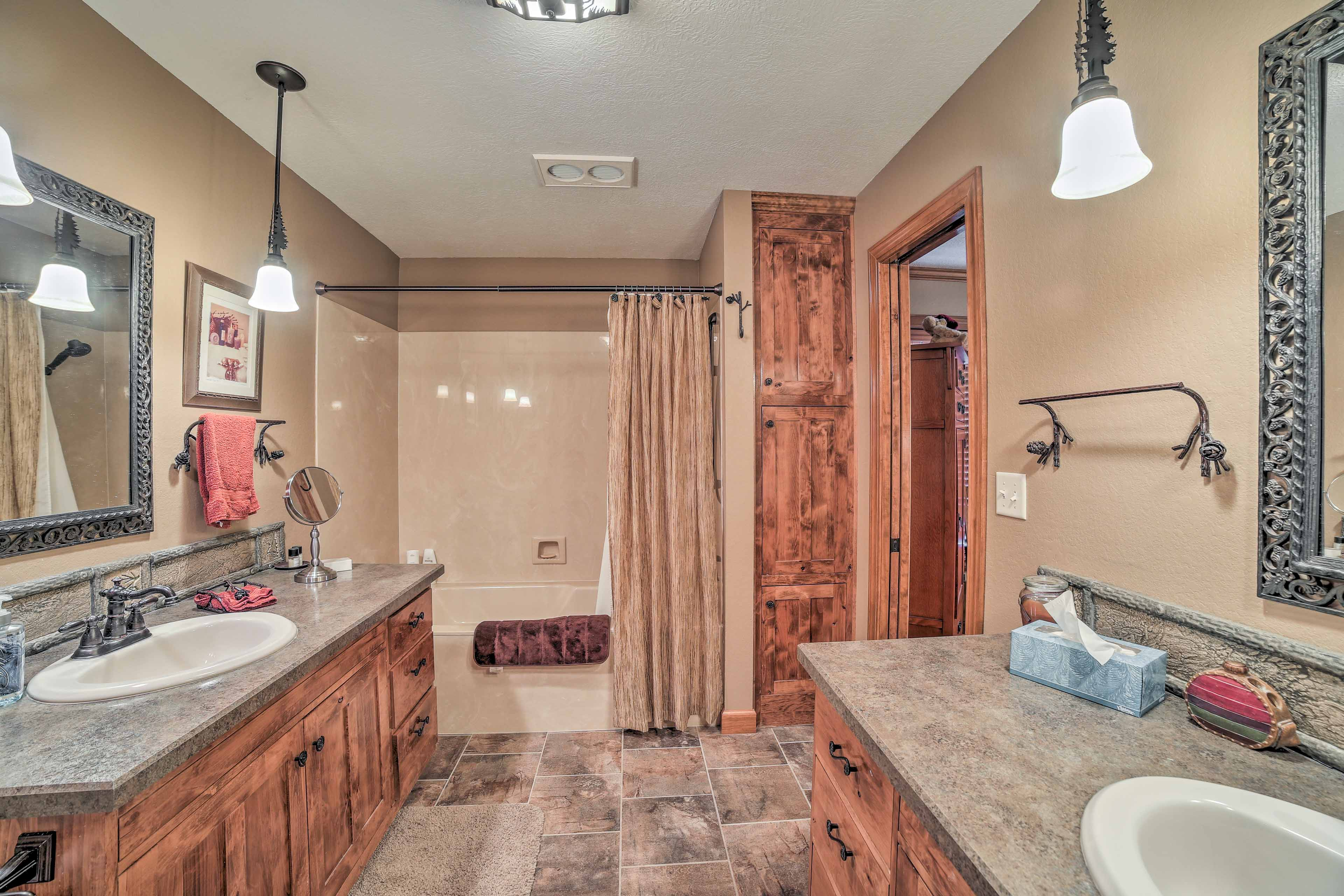 The en-suite bathroom features a shower-tub combo; 2 sinks provide ample space.