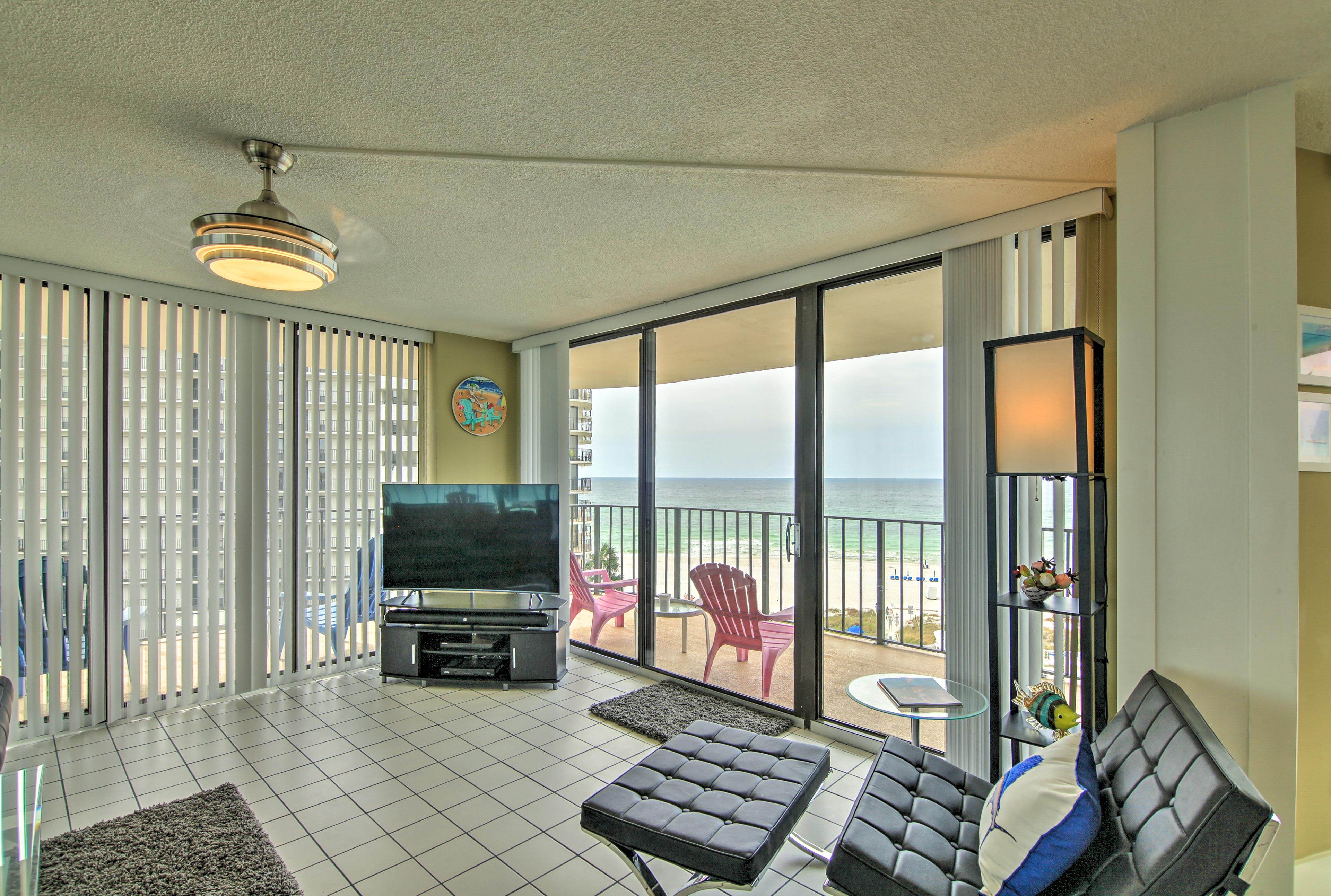 Floor-to-ceiling windows reveal a private balcony and ocean views.