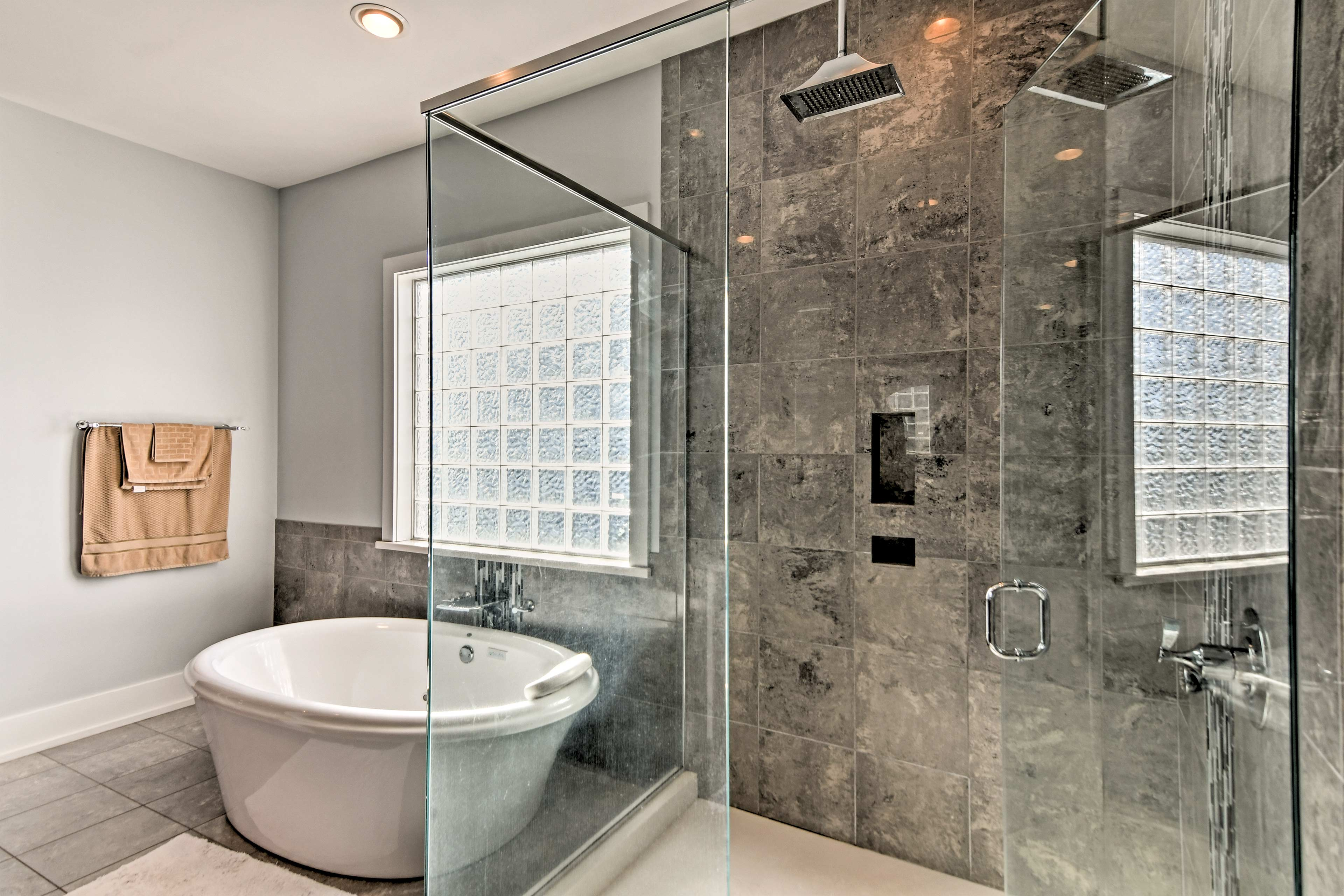 The shower features body jets and a rainfall showerhead.
